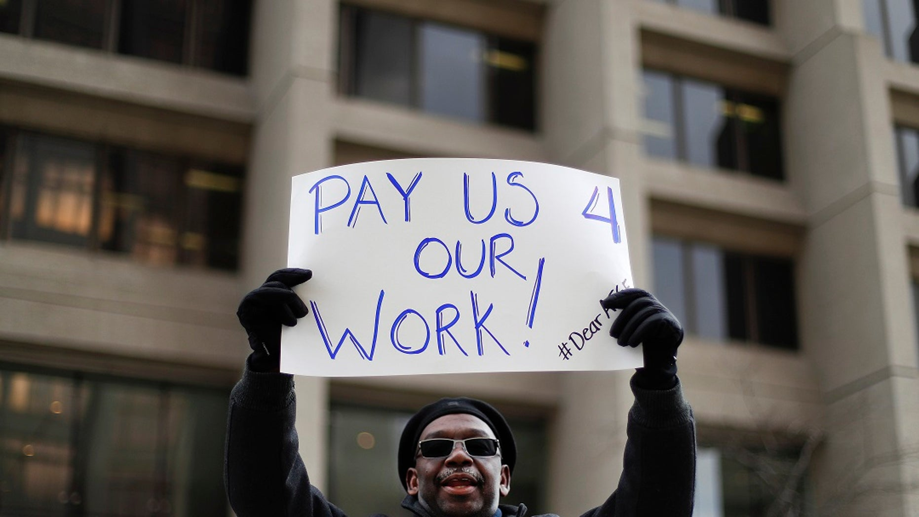 Christopher Belcher, a Department of Veterans Affairs employee, holds a sign during a rally to call for an end to the partial government shutdown, in Detroit, Thursday, Jan. 10, 2019. (Associated Press)