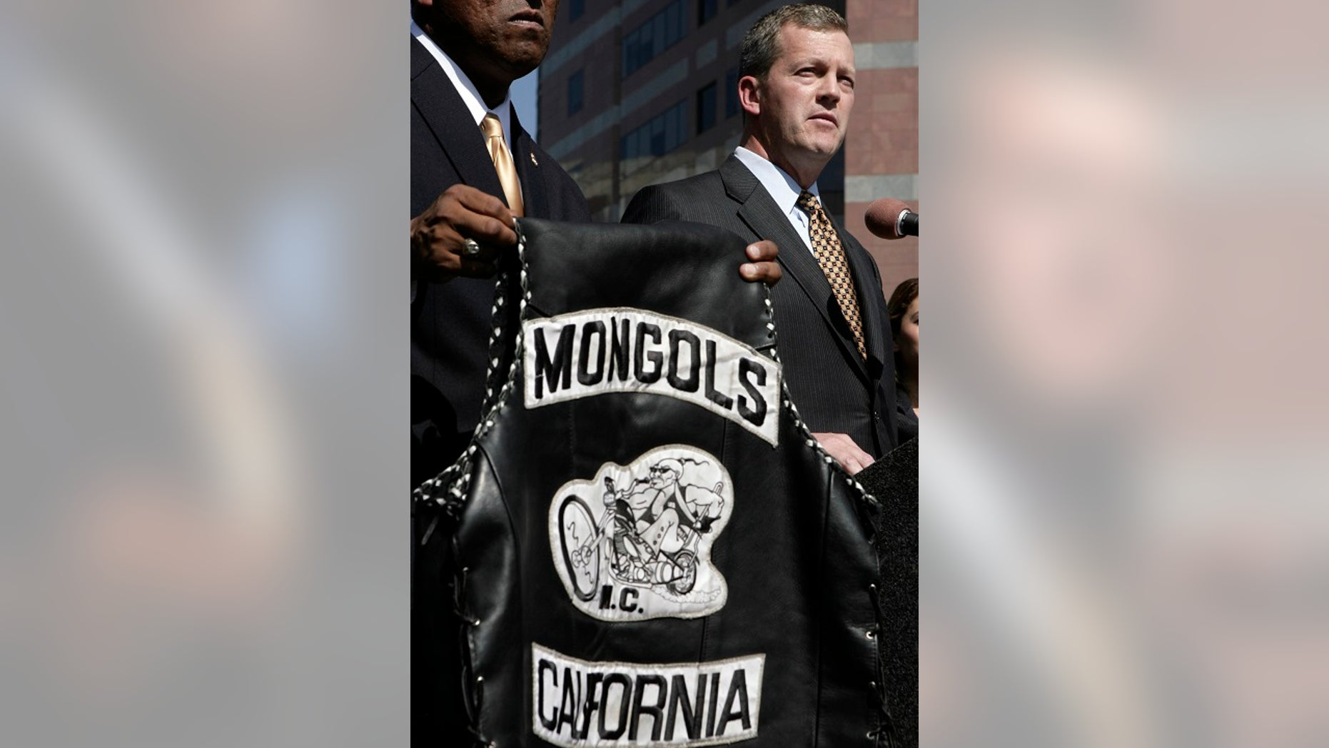 U.S. Attorney Thomas P. O'Brien, right, speaks during a news conference in Los Angeles about the arrest of several Mongol motorcycle gang members in six states as a vest with the Mongols logo displayed. (Associated Press)