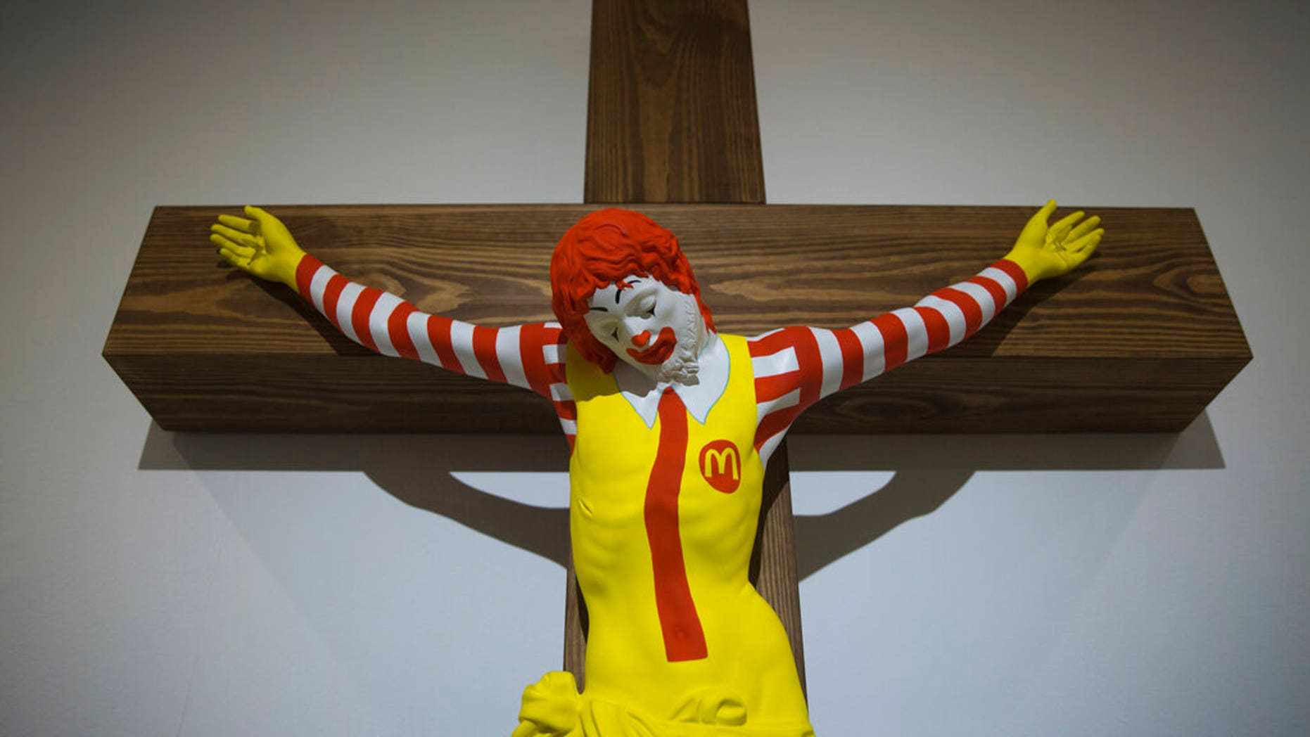 """An artwork called """"McJesus,"""" which was sculpted by Finnish artist Jani Leinonen and depicts a crucified Ronald McDonald, is seen on display as part of the Haifa museum's """"Sacred Goods"""" exhibit, in Haifa, Israel, Monday, Jan. 14, 2019. Hundreds of Christians calling for the sculpture's removal protested at the museum last week. (AP Photo/Oded Balilty)"""
