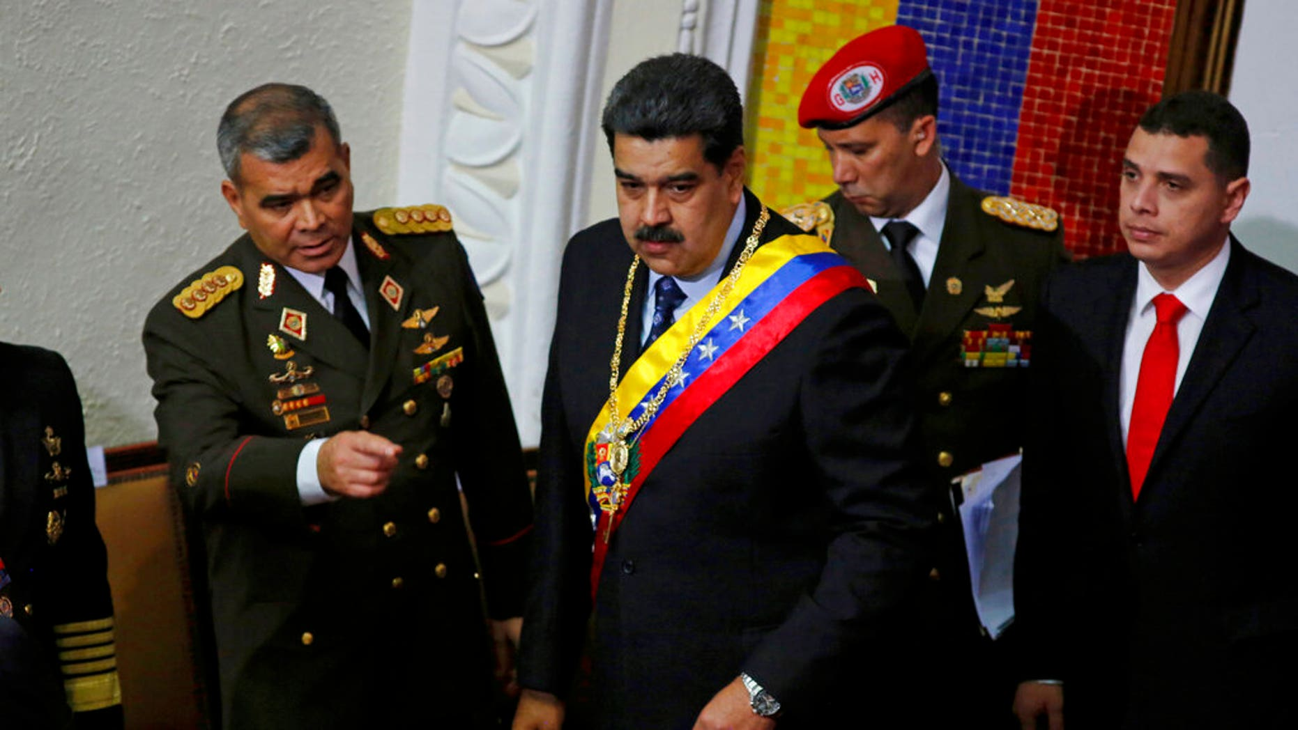 Venezuela's President Nicolas Maduro, center, stands with his Defense Minister Vladimir Padrino Lopez before giving his annual address to the nation to members of the Constitutional Assembly inside the National Assembly in Caracas, Venezuela, Monday, Jan. 14, 2019.