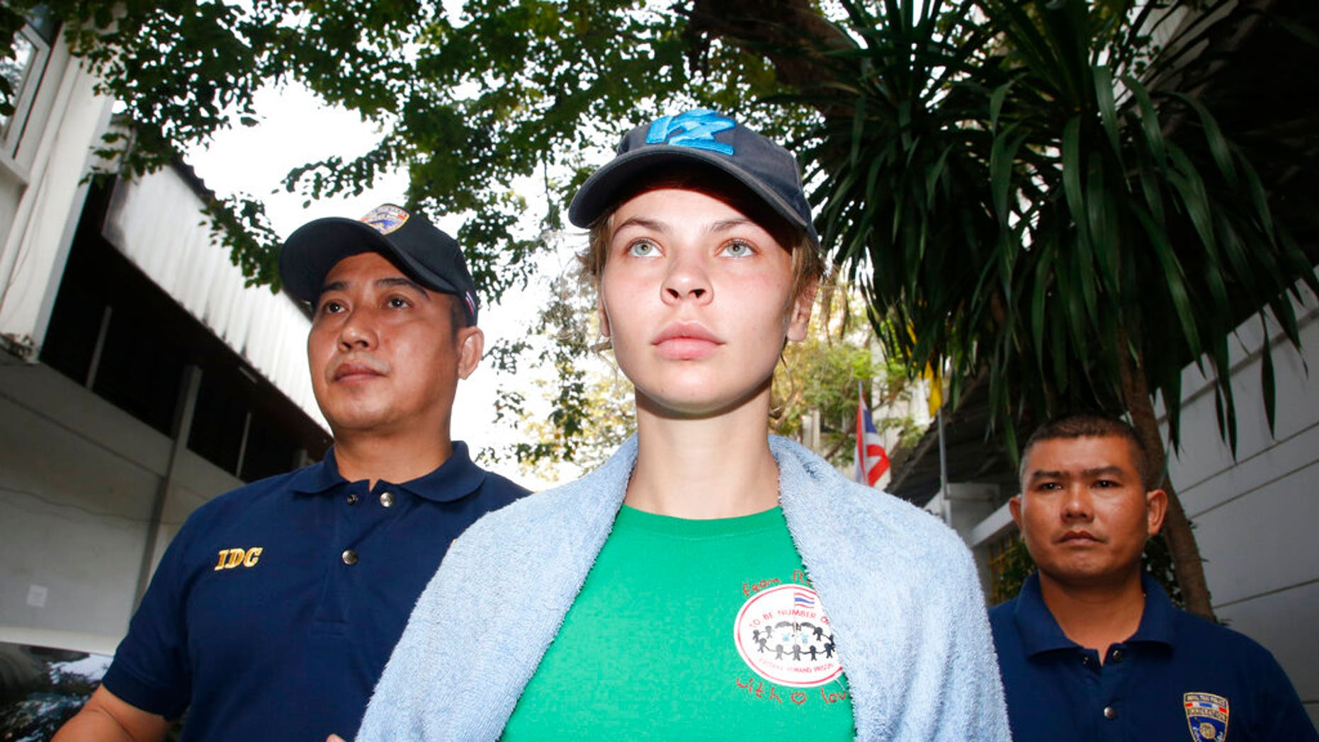 Thai Immigration police officers escort Belarusian model Anastasia Vashukevich, center, from the Immigration Detention Center toward a vehicle to take her to an airport for deportation, in Bangkok, Thailand. (Associated Press)