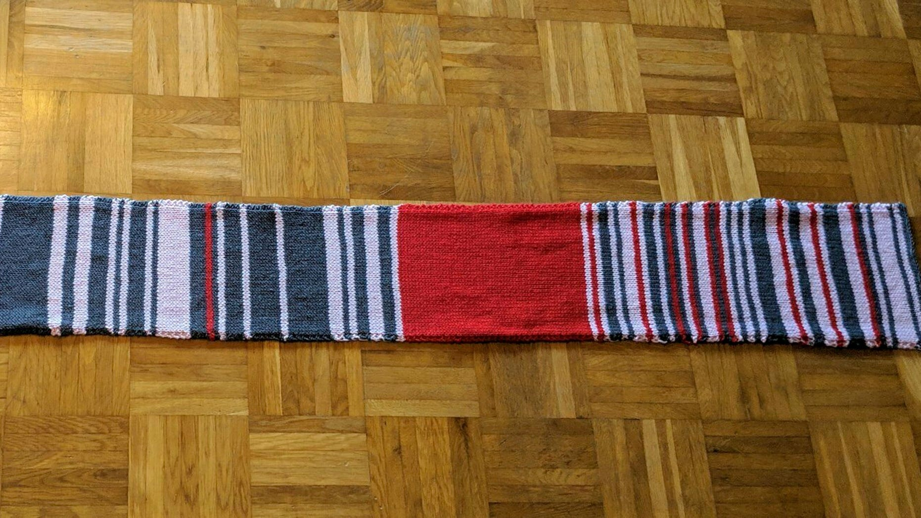 This undated photo made available Thursday Jan. 17, 2019, shows the so called 'delay scarf' which a Munich commuter has knitted with each colour reflecting the amount of time her journey with Deutsche Bahn train service had been delayed. The hand-made scarf sold in an online auction for 7,550 euros (dollars 8,600) to the German Railway Deutsche Bahn. The money is being donated to a charity for the homeless. (Sara Weber via AP)