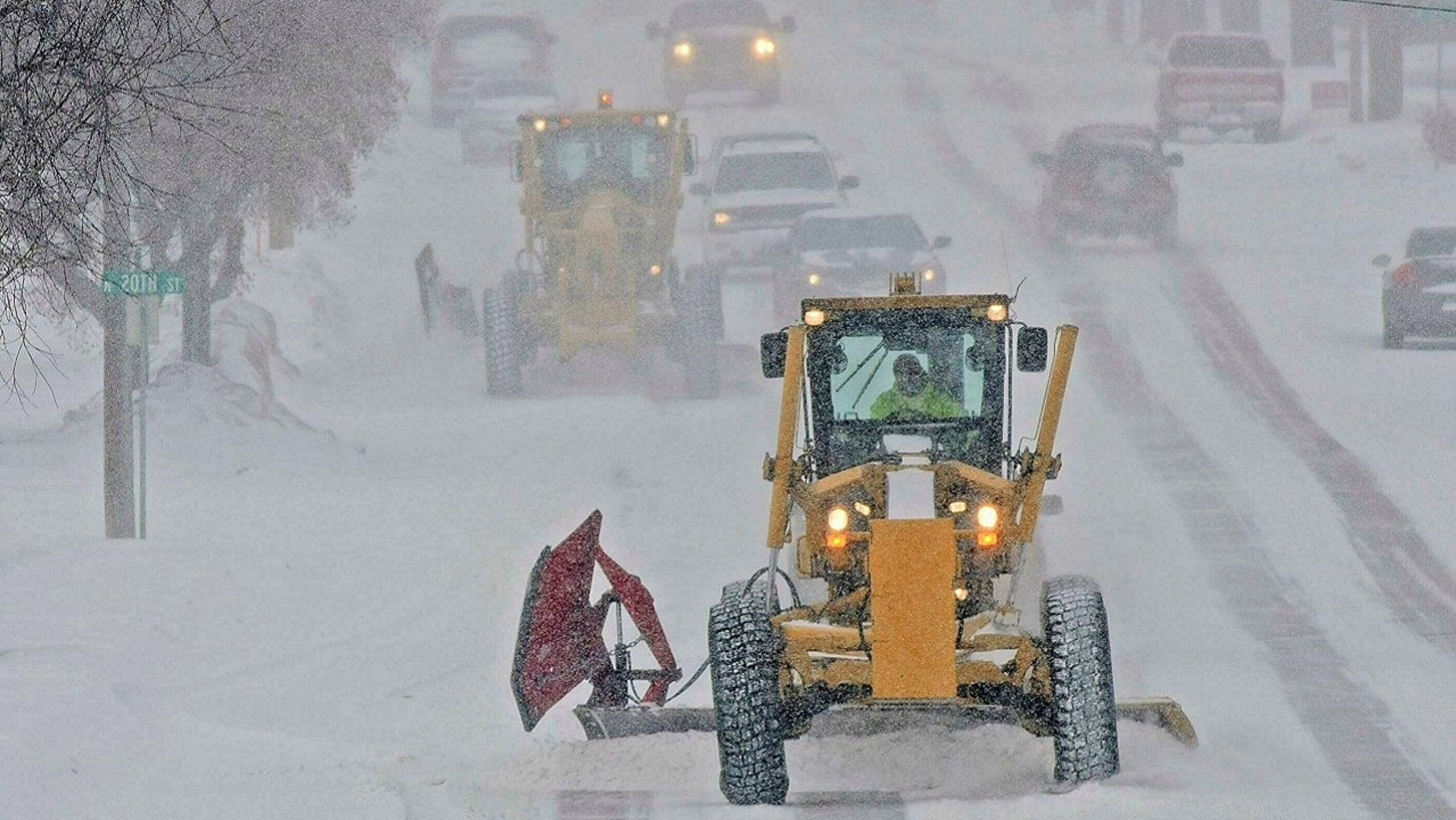Motor graders plow Rosser Avenue as snow falls, Friday, Jan. 18, 2019, in Bismarck, N.D.