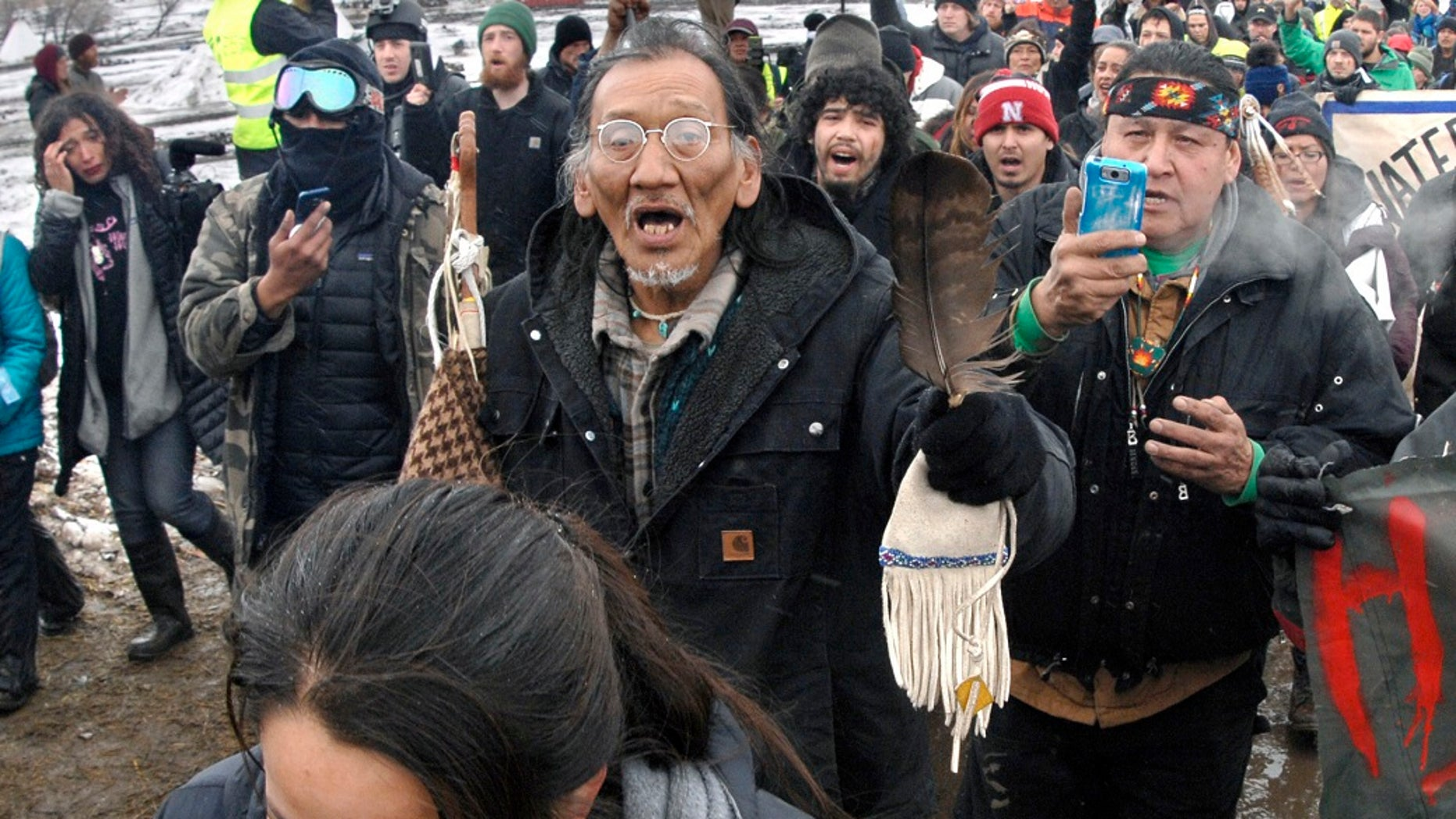 FILE - In this file photo from February 22, 2017, a large crowd marching across the Dakota Access pipeline, including Nathan Phillips, center with goggles, marching out of the Oceti Sakowin camp before the deadline ends up evacuating a large portion of the protesters of the camp near Cannon Ball, ND (Associated Press)