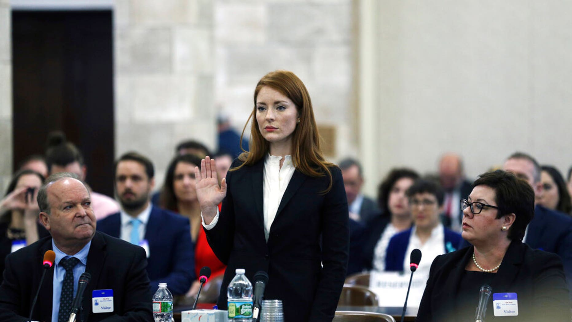 """FILE- In this Dec. 4, 2018, file photo, Katie Brennan, the chief of staff at the New Jersey Housing and Mortgage Finance Agency, raises her hand as she is sworn in to testify before the Select Oversight Committee at the Statehouse, in Trenton, On Wednesday, the Middlesex County Prosecutor's office said that it would not be filing charges against Albert Alvarez, whom Brennan accused of sexually assaulting her in 2017, when they were both working to get Gov. Phil Murphy elected, citing """"a lack of credible evidence."""" (AP Photo/Mel Evans, File)"""