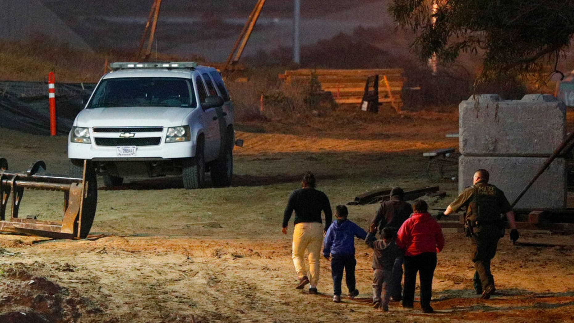 FILE - In this Dec. 3, 2018, file photo, migrants are escorted by a U.S. Border Patrol agent as they are detained after climbing over the border wall from Playas de Tijuana, Mexico, to San Ysidro, Calif. (AP Photo/Rebecca Blackwell, File)