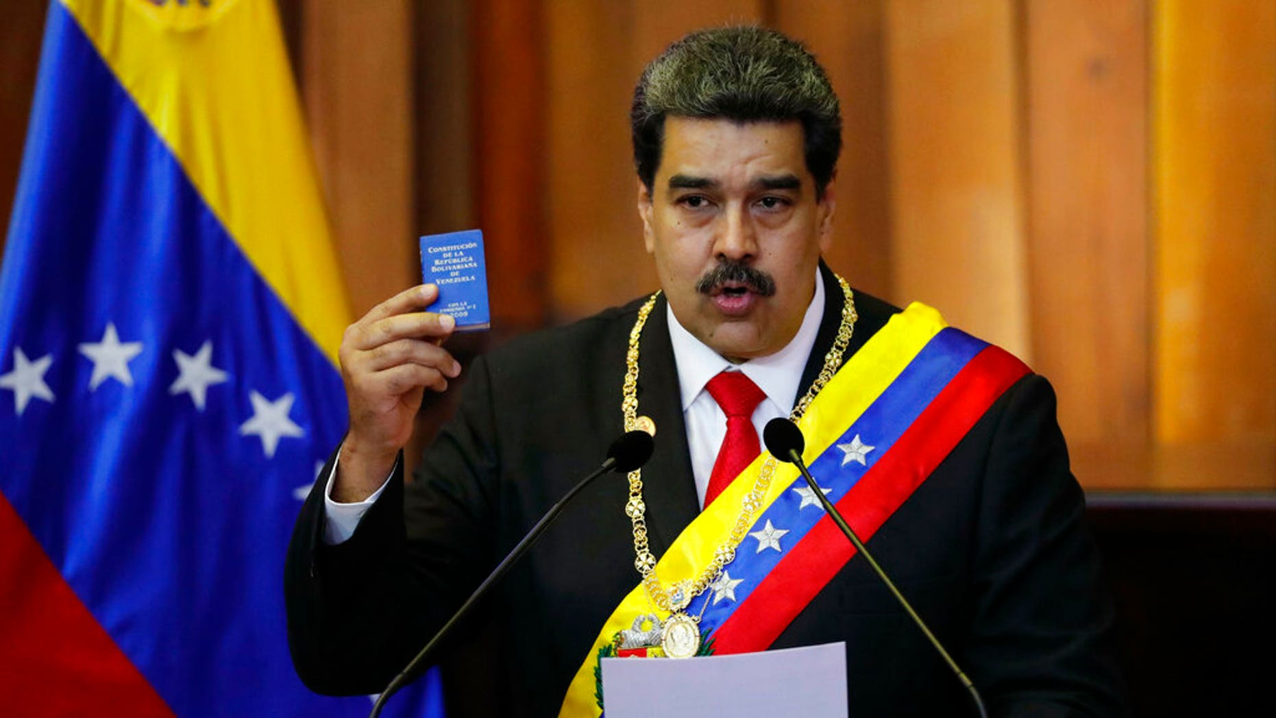 FILE - In this Jan. 10, 2019, file photo, Venezuela's President Nicolas Maduro holds up a small copy of the constitution as he speaks during his swearing-in ceremony at the Supreme Court in Caracas, Venezuela. (AP