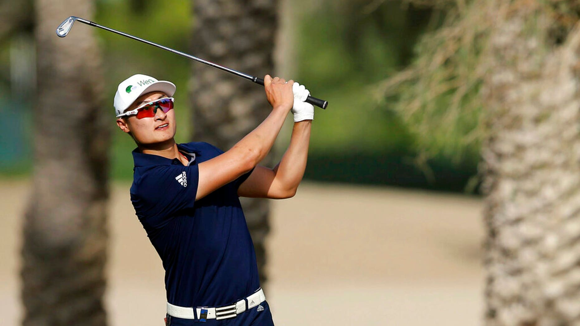 Haotong Li follows his ball on the 14th hole during the third round of the Dubai Desert Classic Golf Tournament in Dubai, United Arab Emirates.
