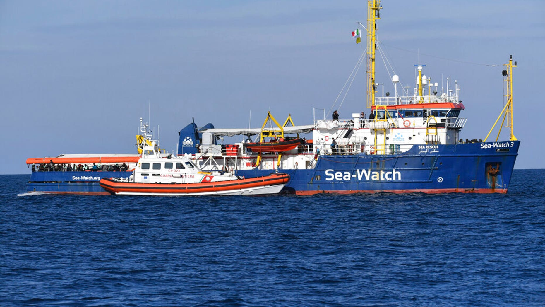 A Coast Guard boat approaches a German humanitarian group's rescue boat Sea Watch 3, to deliver food and blankets for the cold, off the coast of Syracuse, Italy, Sunday, Jan. 27, 2019. (AP Photo/Salvatore Cavalli)