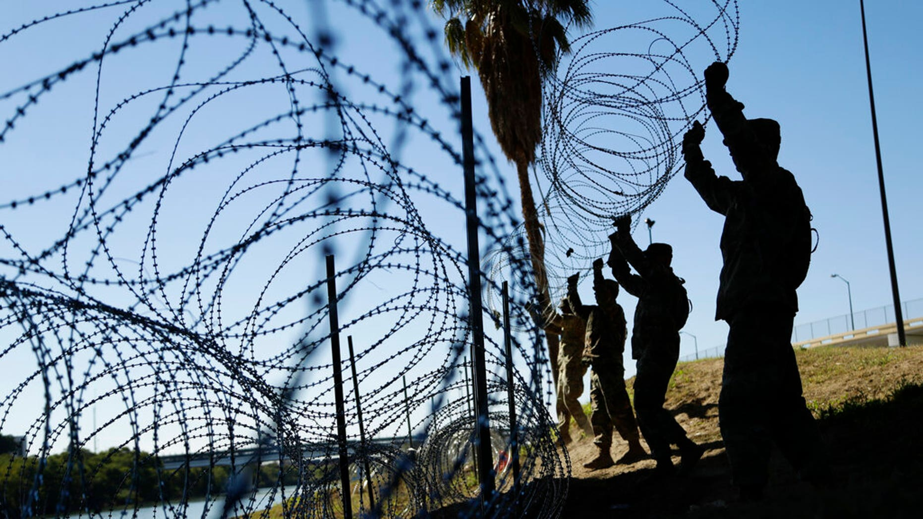 In this Nov. 16, 2018, file photo, members of the U.S. military install multiple tiers of concertina wire along the banks of the Rio Grande near the Juarez-Lincoln Bridge at the U.S.-Mexico border in Laredo, Texas.  (AP Photo/Eric Gay, File)