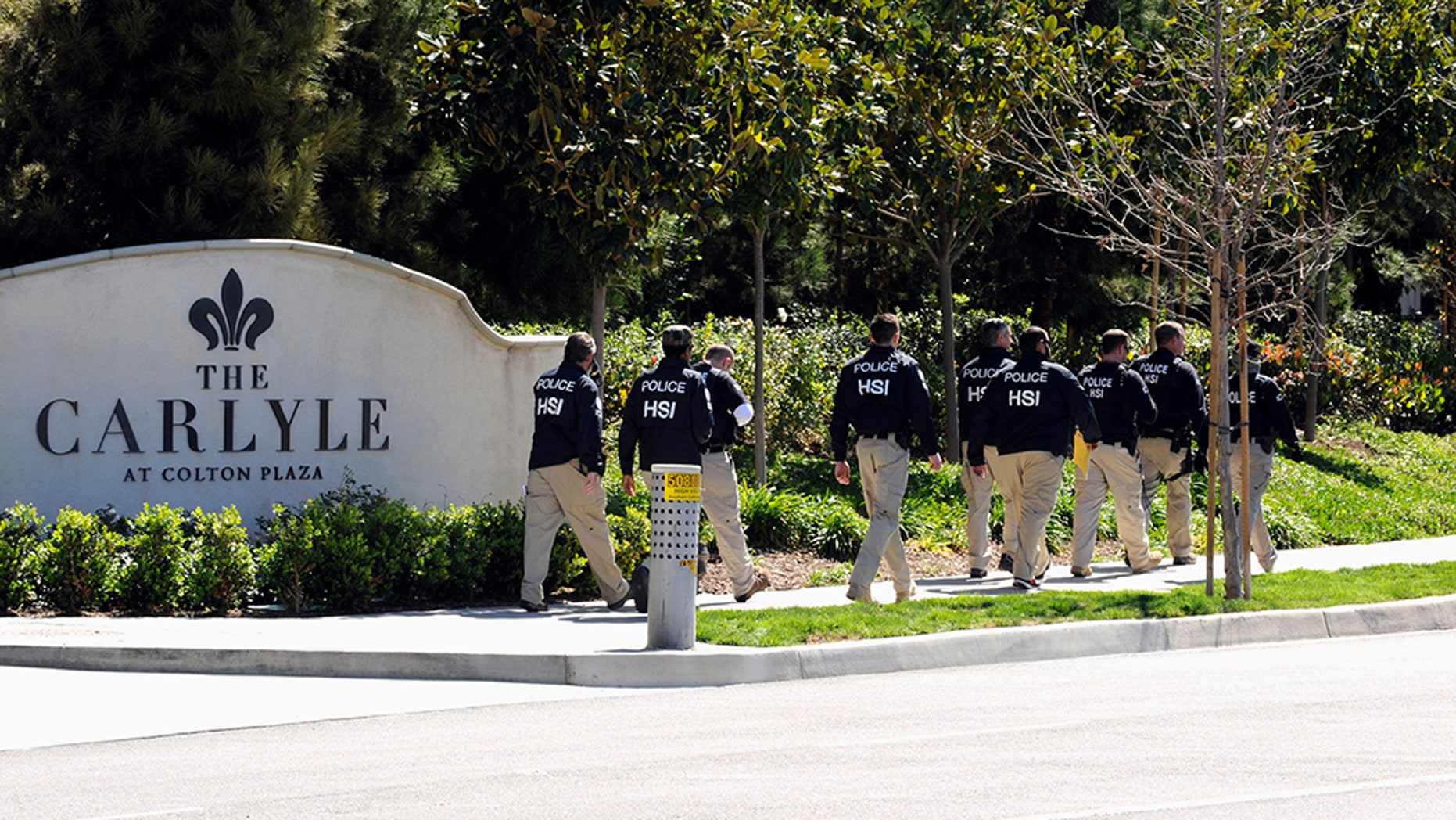 """Federal agents walk past Carlyle Apartments, a location suspected of involvement in """"maternity tourism"""" schemes, in Irvine March 3, 2015. (REUTERS/Bob Riha Jr.)"""