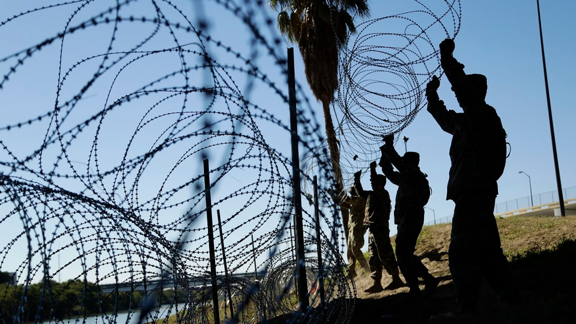 Members of the U.S. military install multiple tiers of concertina wire along the banks of the Rio Grande near the Juarez-Lincoln Bridge at the U.S.-Mexico border in Laredo, Texas, Nov. 16, 2018. (Associated Press)