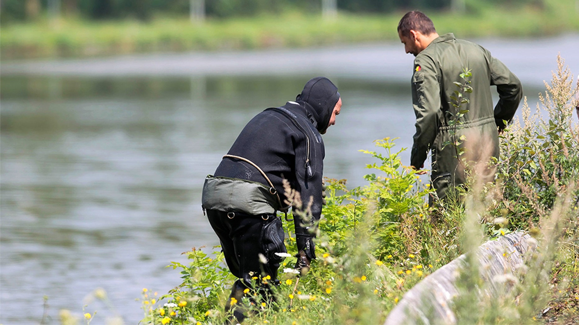 """A diver gets out of the canal in Ronquieres, some 30 kms south of Brussels on August 3, 2010 during a search for evidence in the """"Brabant's killers"""" (Tueurs du Brabant - Bende van Nijvel) case. This is the second search of the area since 1986, a few months after the last killings at the Delhaize supermarket in Aalst. Investigating police officers, divers from the army, DVI (victim identification cell) members and members of civilian protection were part of the search operation. (VIRGINIE LEFOUR/AFP/Getty Images)"""