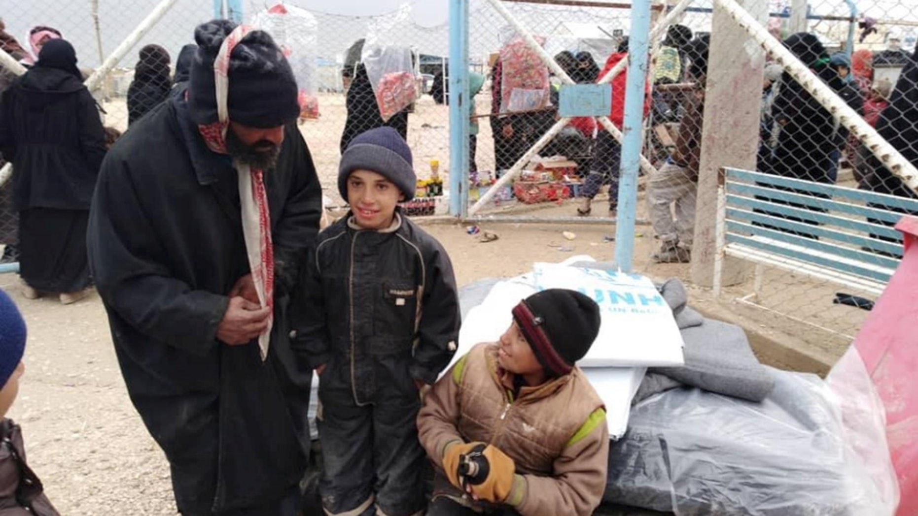 Newly displaced Syrian children and men wait to receive UNHCR tarpaulins and other aid at Al Hol camp in Hassakeh, Syria.