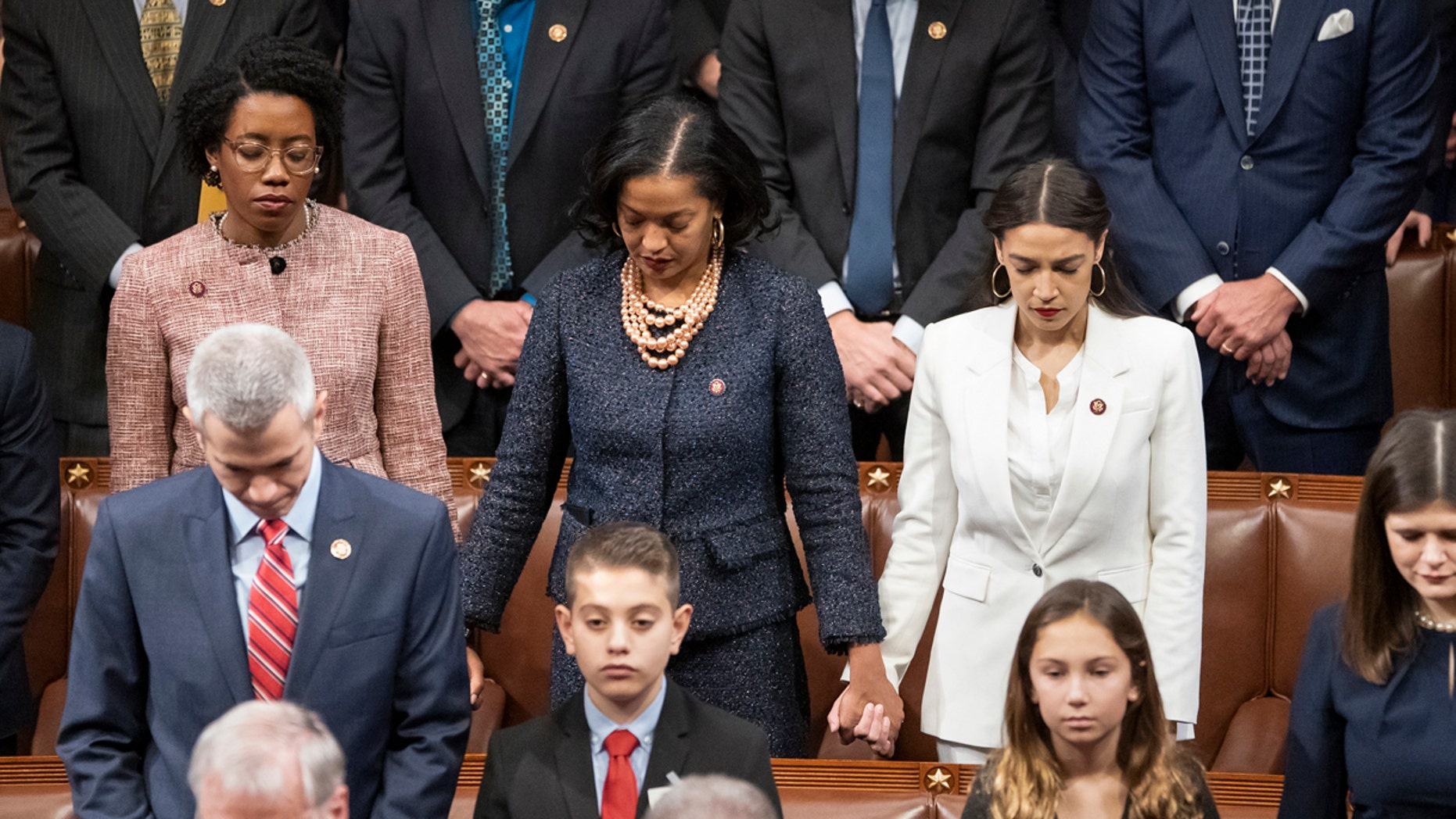 From left in center row, Rep. Lauren Underwood, D-Ill., Rep. Jahana Hayes, D-Conn., and Rep. Alexandria Ocasio-Cortez, D-N.Y, hold hands during an opening prayer as the House of Representatives assembles for the first day of the 116th Congress at the Capitol in Washington, Thursday, Jan. 3, 2019. (AP Photo/J. Scott Applewhite)