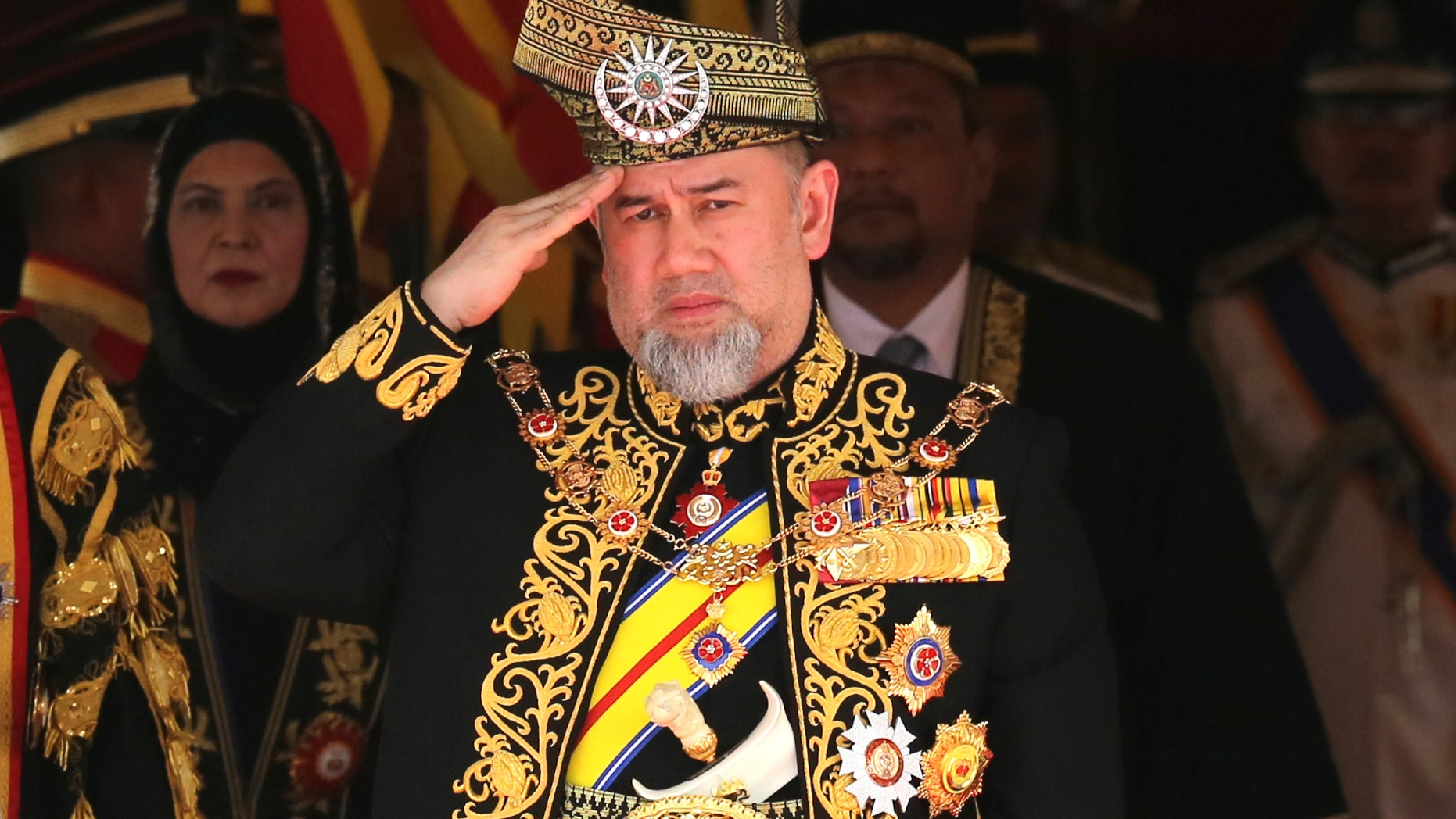 FILE - In this July 17, 2018, file photo, Malaysian King Sultan Muhammad V salutes during the national anthem at the opening of the 14th parliament session at the Parliament house in Kuala Lumpur, Malaysia. Malaysia King Sultan Muhammad V has abdicated in an unexpected and rare move, just after two years on the throne. The palace said in a statement on Sunday, Jan. 6, 2019, that Sultan Muhammad V, 49, has resigned with immediate effect, cutting short his five-year term, without giving any reasons. Sultan Muhammad V, ruler of northeast Kelantan state, was installed in December 2016 as one of the country's youngest constitutional monarchs. (AP Photo/Yam G-Jun, File)