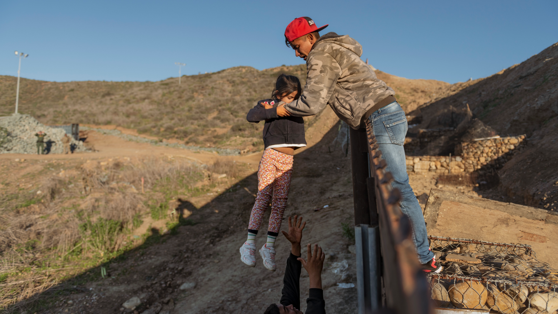 Jan 3: A migrant from Honduras pass a child to her father after he jumped the border fence to get into the U.S. side to San Diego, Calif., from Tijuana (AP Photo/Daniel Ochoa de Olza)