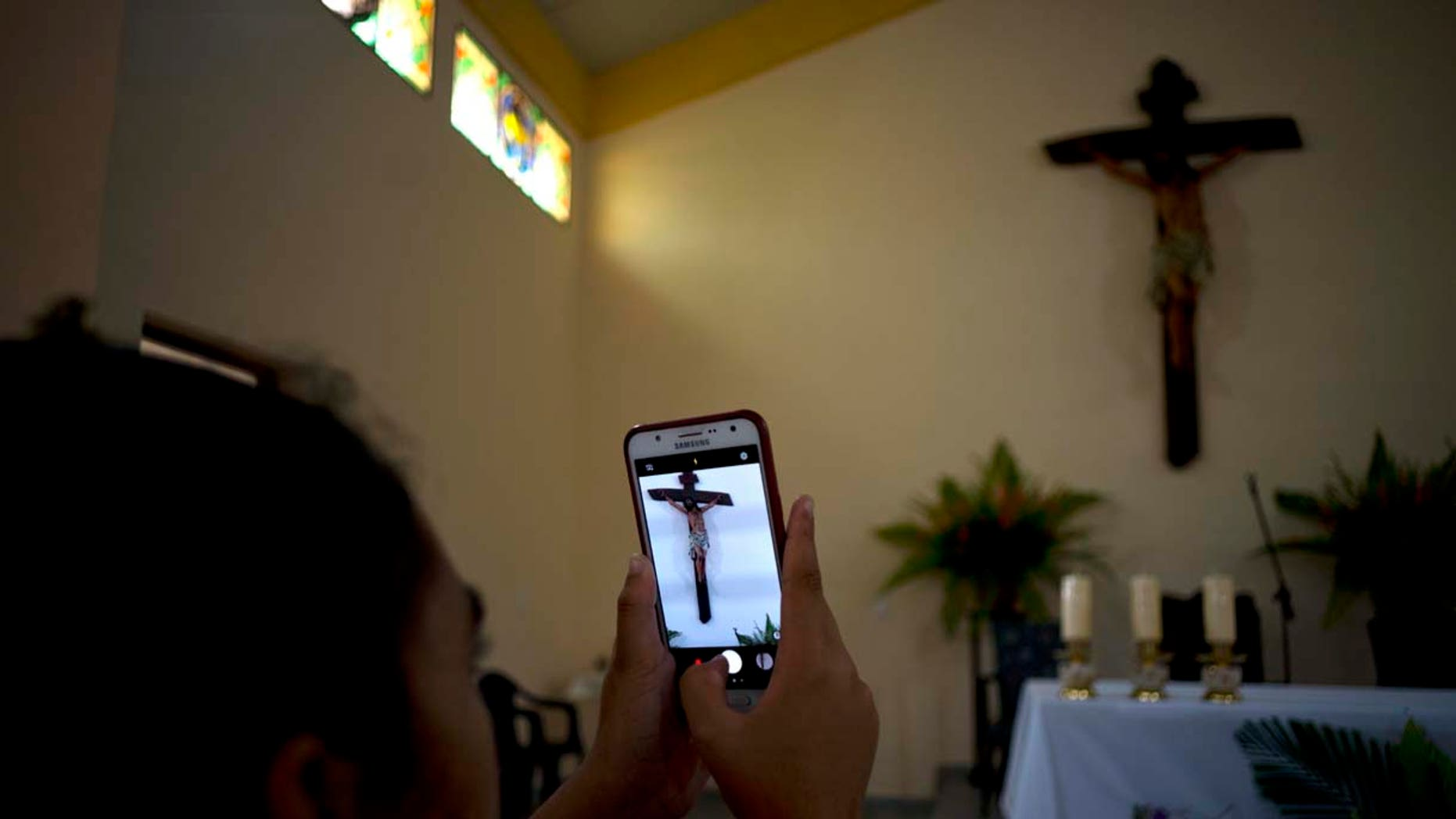 A parishioner makes a photo of the crucifix above the altar at the newly consecrated Sagrado Corazon de Jesus, or Sacred Heart, Catholic church, in Sandino, Cuba, Saturday, Jan. 26, 2019. (AP Photo/Ramon Espinosa)