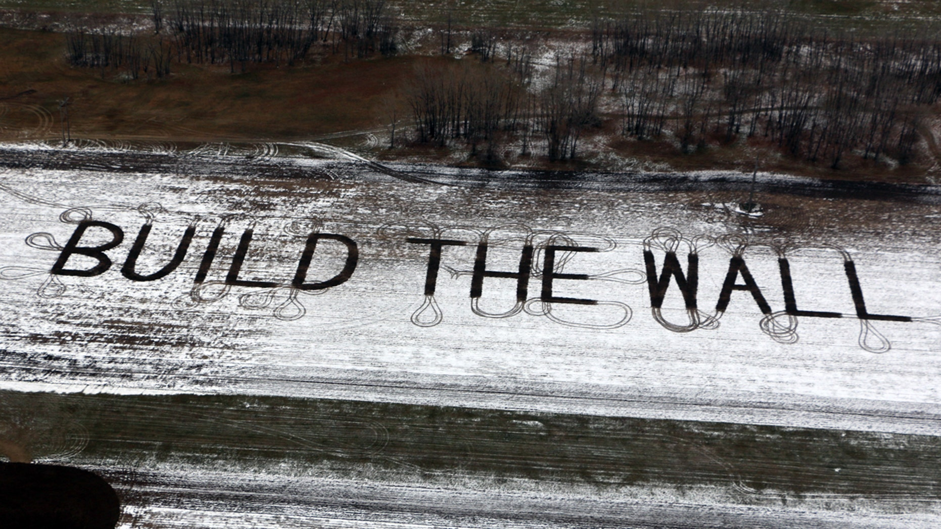 """Farmer Gene Hanson of Edgeley, North Dakota plowed a message of support for President Trump: """"Build the wall."""""""