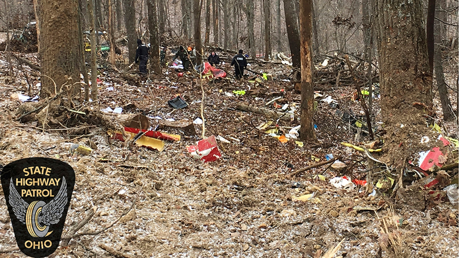 In this photo provided by the Ohio State Highway Patrol, authorities survey the scene of wreckage where a medical helicopter crashed in a remote wooded area in Brown Township, Ohio, on Tuesday on its way to pick up a patient. (Ohio State Highway Patrol via AP)