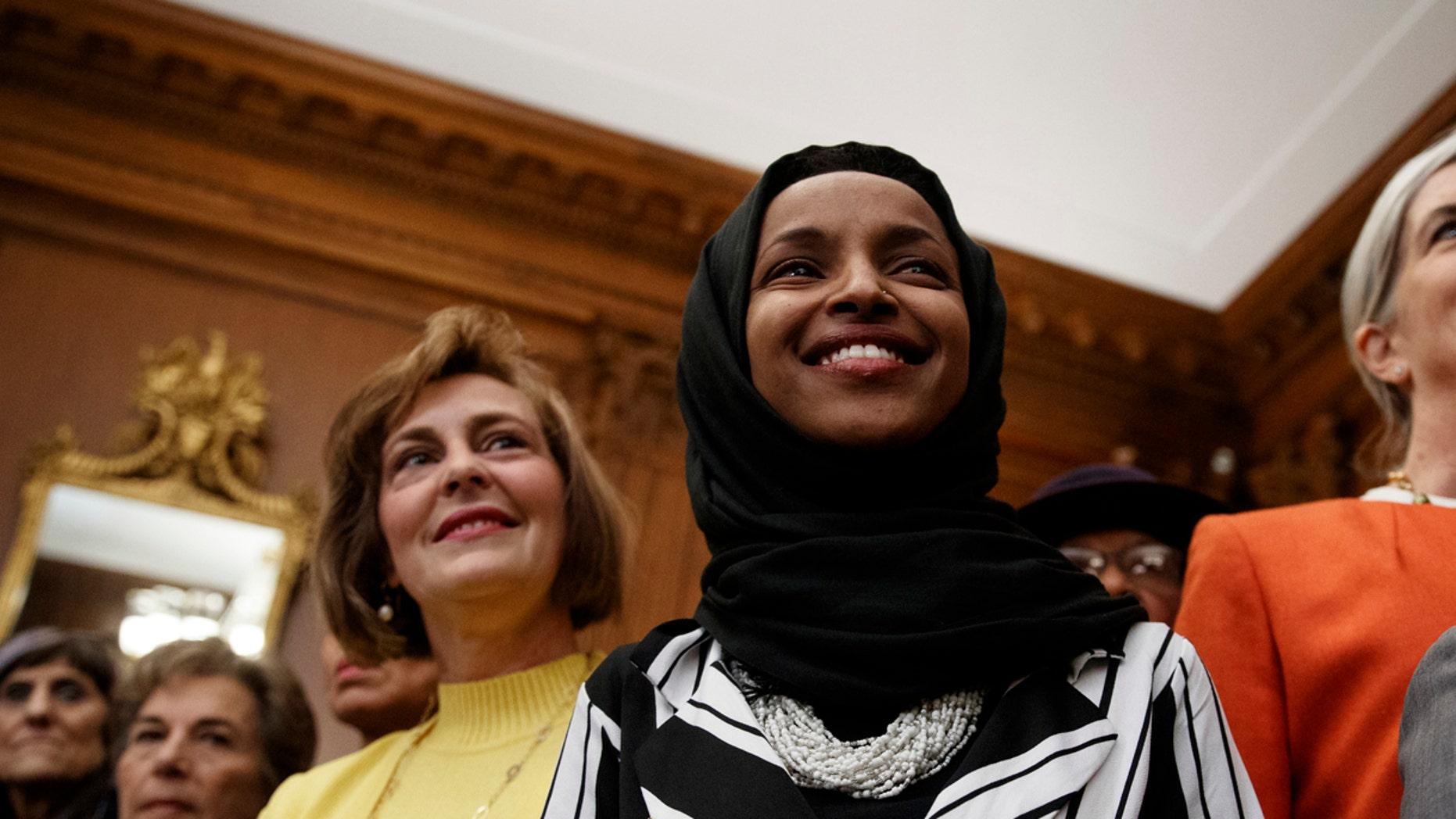 Rep. Ilhan Omar, D-Minn., center, joins other Democrats during a news conference on Capitol Hill in Washington, Friday, Jan. 4, 2019, about the introduction of H.R. 1 - For the People Act. (AP Photo/Carolyn Kaster)