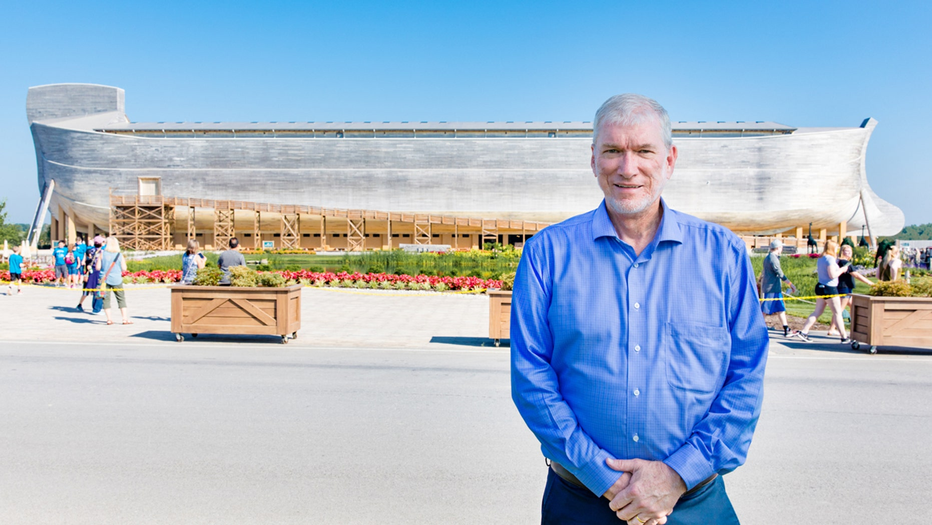 Ken Ham, president and founder of Answers in Genesis, the Creation Museum, and the Ark Encounter, stands in front of a full-size Noah's Ark replica.