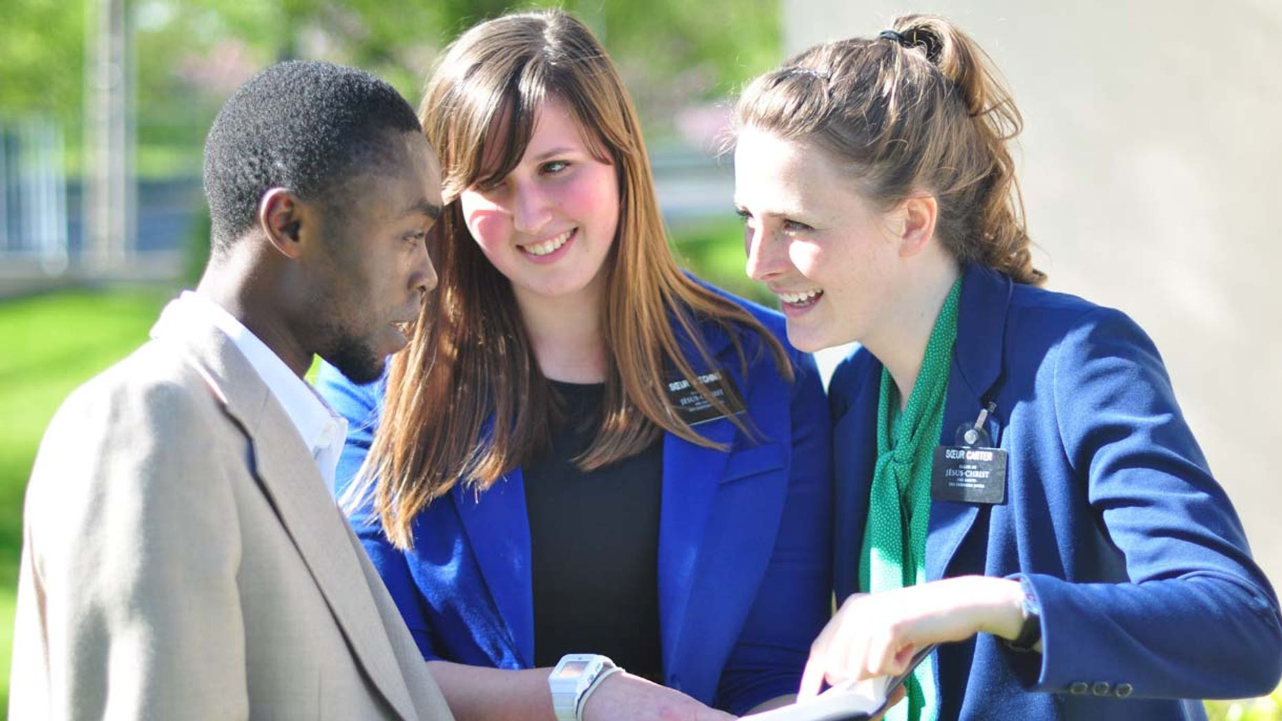 Sister missionaries teaching a young man in Lyon, France.