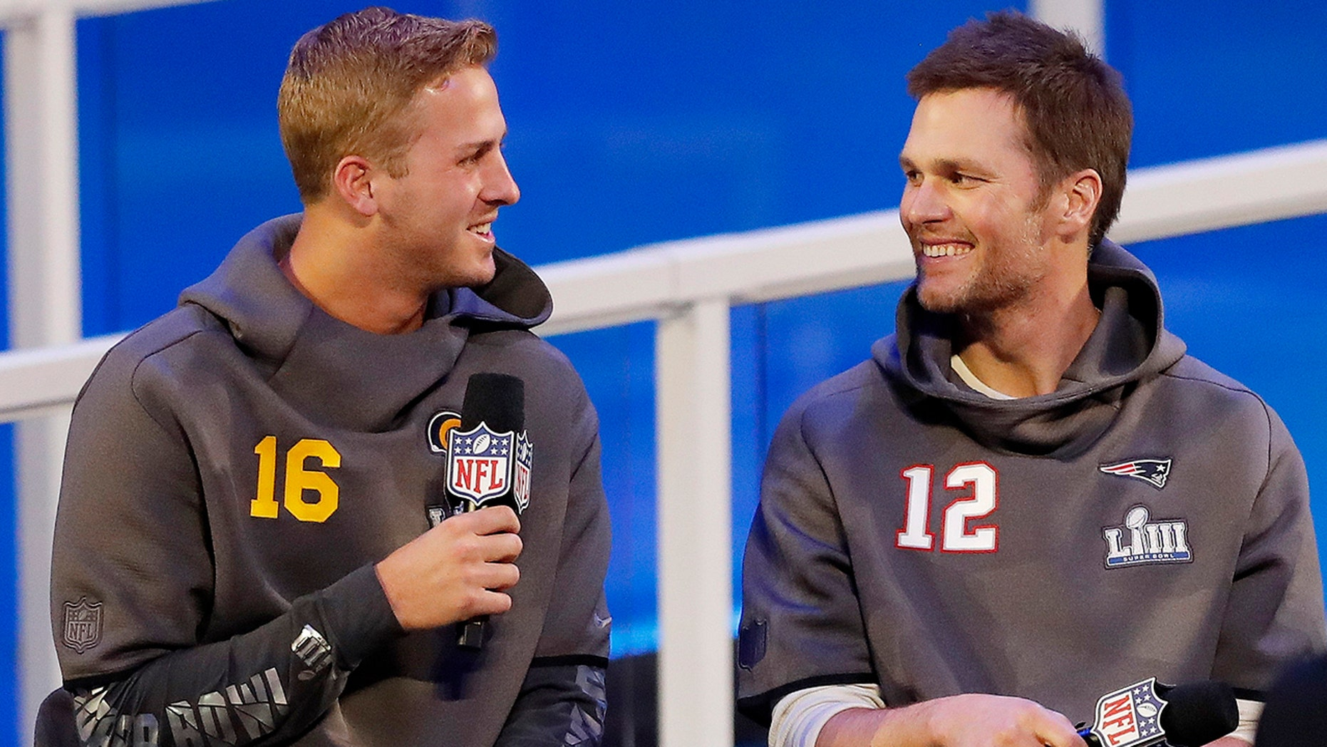 Los Angeles Rams' Jared Goff talks to New England Patriots' Tom Brady during Opening Night for the NFL Super Bowl 53 football game Monday, Jan. 28, 2019, in Atlanta. (AP Photo/John Bazemore)