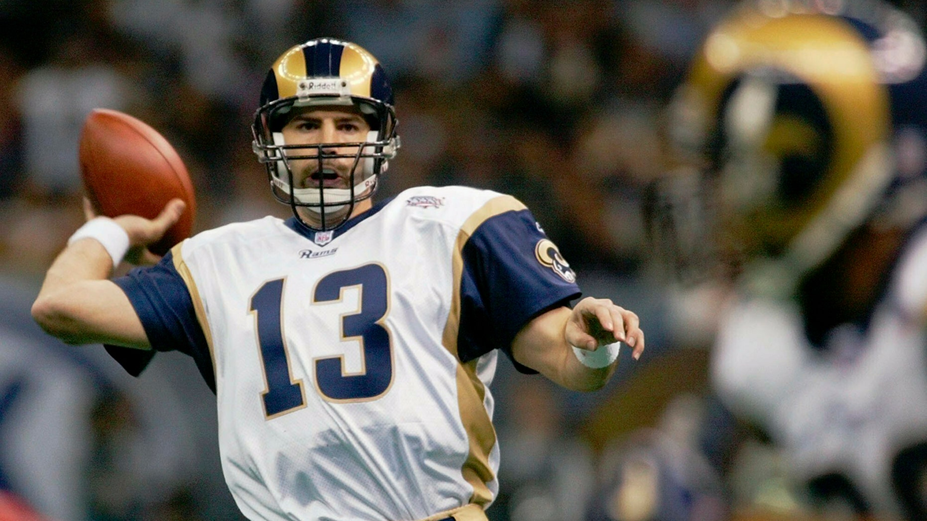 FILE - In this Feb. 3, 2002, file photo, St. Louis Rams quarterback Kurt Warner looks to pass to Marshall Faulk, right, in the first quarter against the New England Patriots in Super Bowl 36 in New Orleans.