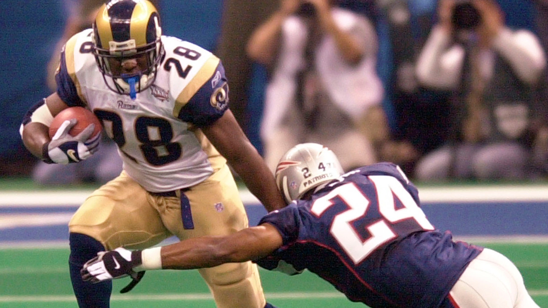 File-This Feb. 3, 2002, file photo shows St. Louis Rams running back Marshall Faulk (28) fending of New England Patriots cornerback Ty Law (24) during first-quarter play of Super Bowl XXXVI in New Orleans.