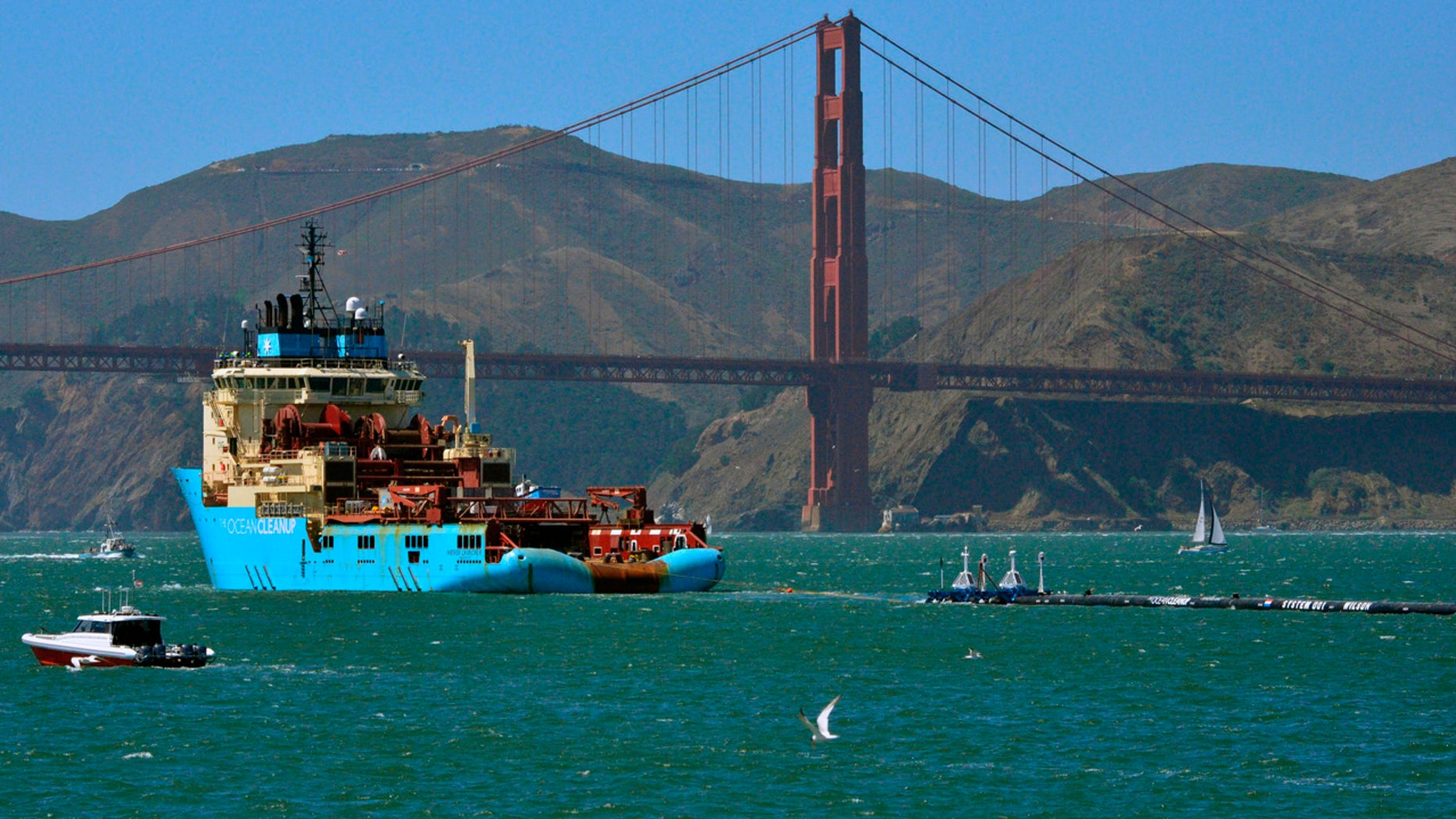 FILE- In this Sept. 8, 2018 file photo, a ship tows The Ocean Cleanup's first buoyant trash-collecting device toward the Golden Gate Bridge in San Francisco en route to the Pacific Ocean. (AP Photo/Lorin Eleni Gill, File)