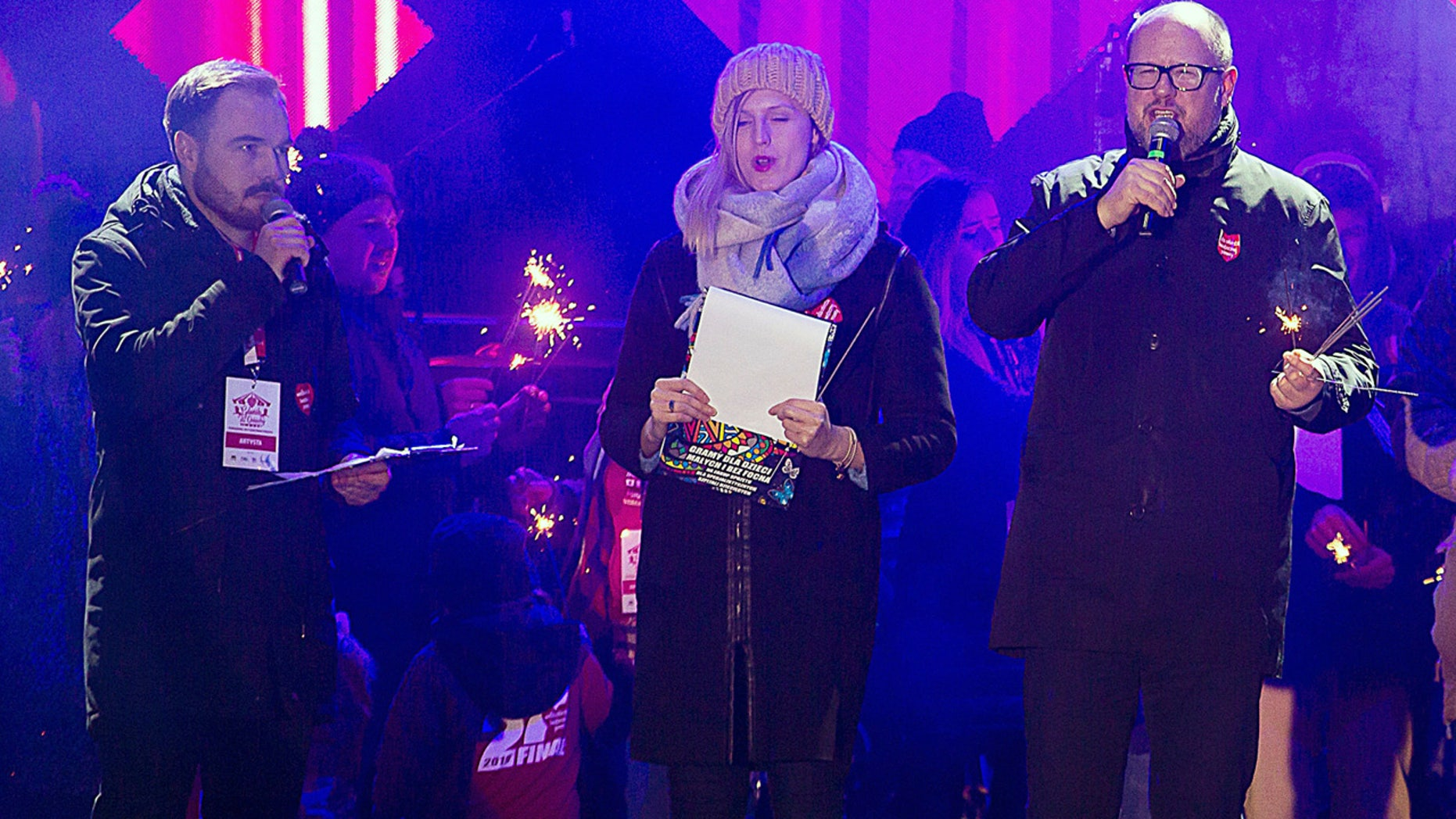 Gdansk Mayor Pawel Adamowicz, far right, speaks to an audience shortly before he was stabbed in Gdansk, Poland, on Sunday, Jan. 13, 2019. Adamowicz was taken to a hospital in very serious condition after the attack and underwent surgery. (AP Photo/Anna Rezulak/KFP) POLAND AUT