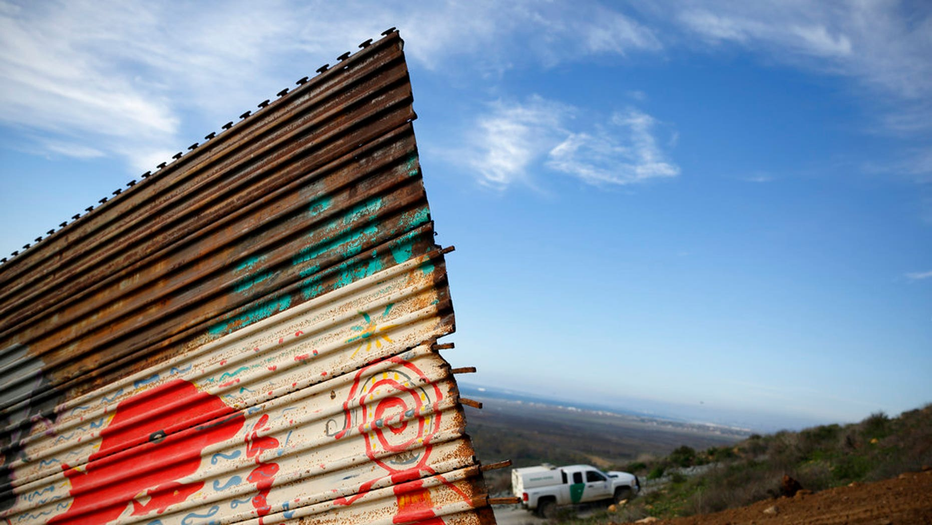 """A U.S. Border Patrol vehicle passes behind a section of border wall Wednesday, Jan. 9, 2019, seen from Tijuana, Mexico. U.S. President Donald Trump walked out of his negotiating meeting with congressional leaders Wednesday — """"I said bye-bye,"""" he tweeted— as efforts to end the 19-day partial government shutdown fell into deeper disarray over his demand for billions of dollars to build a wall on the U.S.-Mexico border. (AP Photo/Gregory Bull)"""