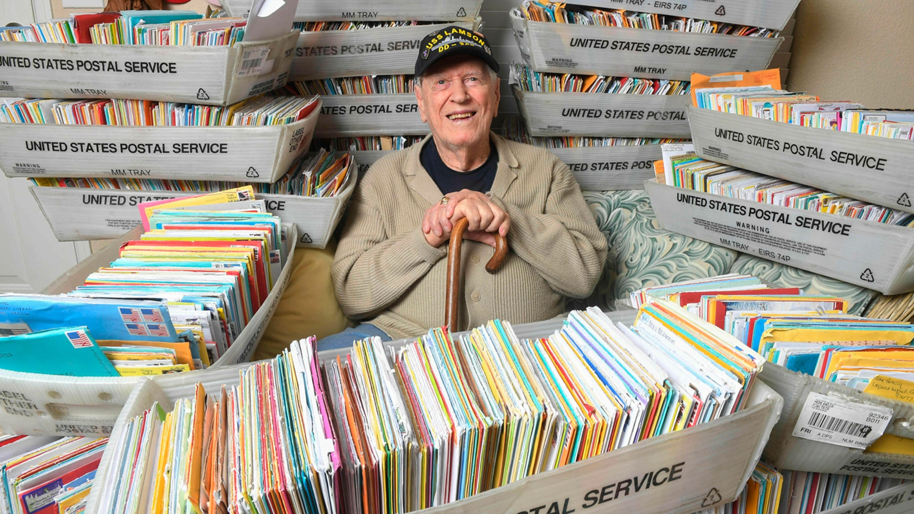 In this Tuesday, Jan. 8, 2019 photo, Duane Sherman, 96, poses at home with a small fraction of the 50,000 birthday cards he's received after his daughter's social media request for people to send him cards to cheer him up on his birthday went viral in Fullerton, Calif.