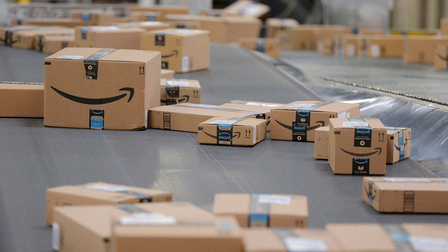 Packages emblazoned with Amazon logos travel along a conveyor belt inside of an Amazon fulfillment center. (Reuters)