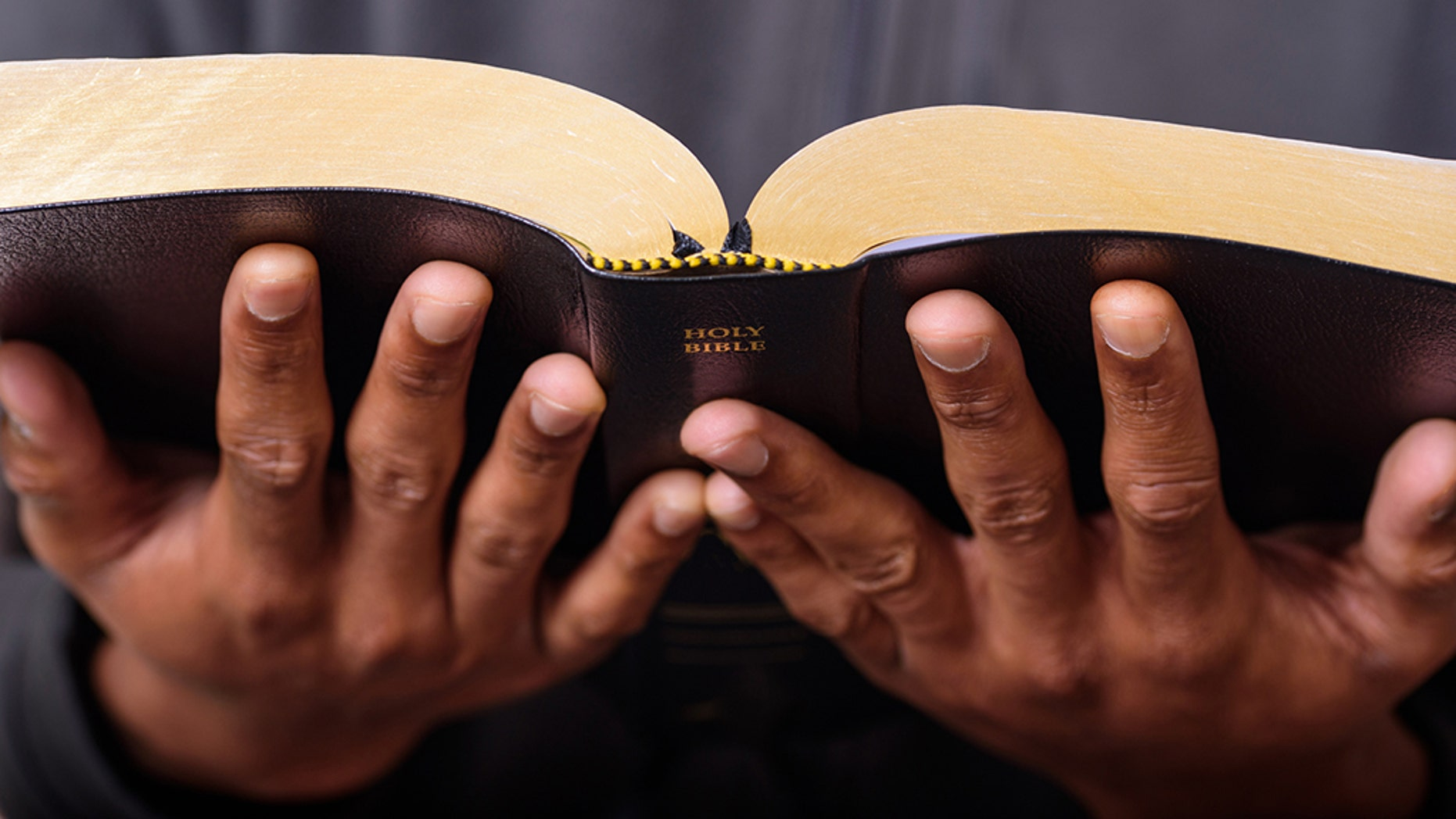 A close up view of a man hands holding the Holy Bible, Worship Concept