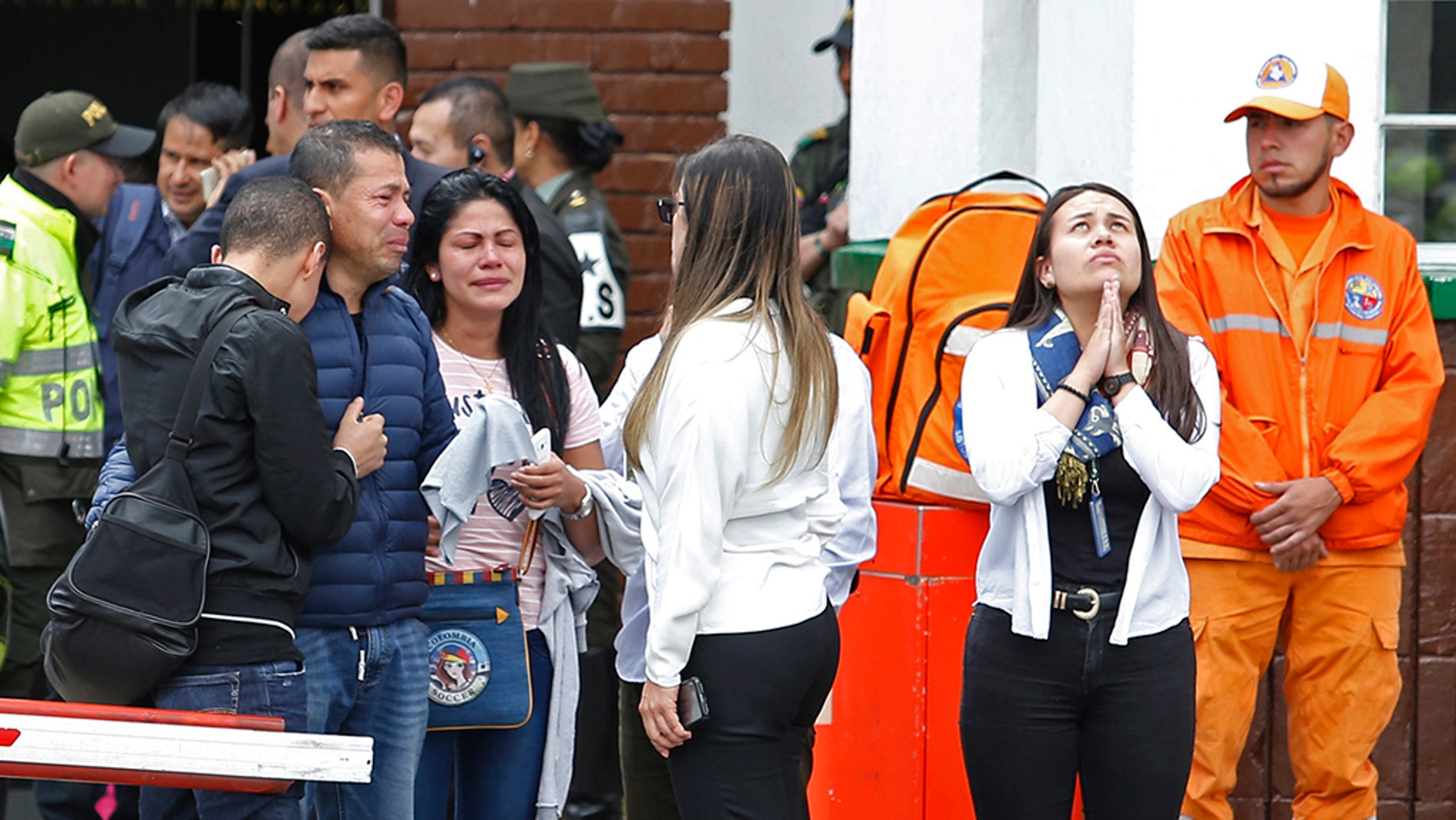 Family members of victims of a bombing gather outside the entrance to the General Santander police academy where the bombing took place in Bogota, Colombia, Thursday.