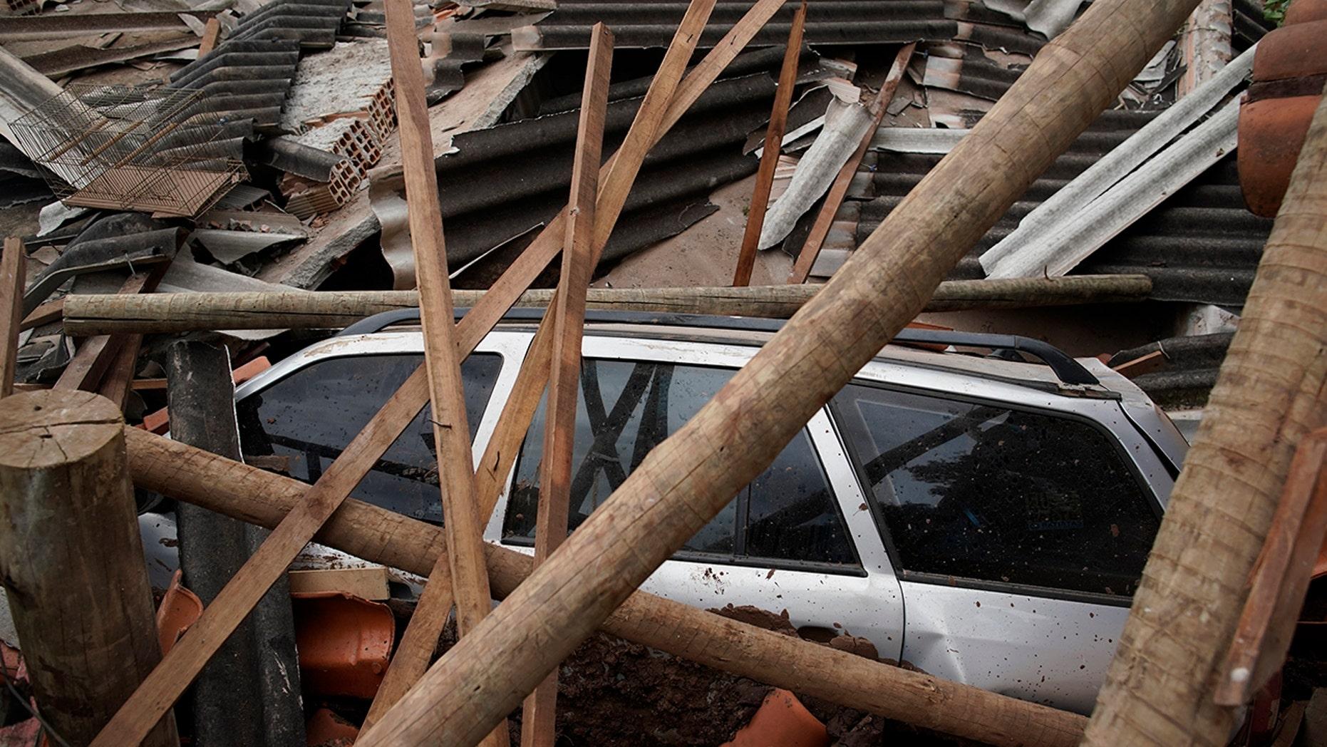 A car lies covered in debris after a dam collapse near Brumadinho, Brazil, Saturday, Jan. 26, 2019. (Associated Press)