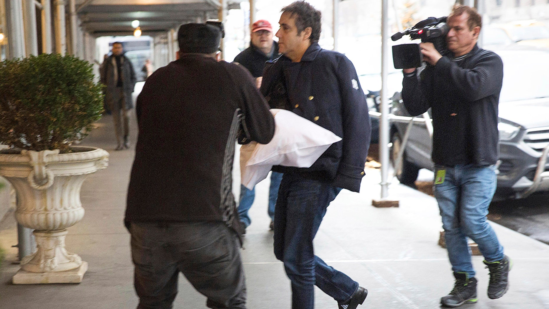 Michael Cohen arrives at his home in New York City with one of his arms in a sling supported by a pillow Friday, Jan. 18, 2019. (Associated Press)