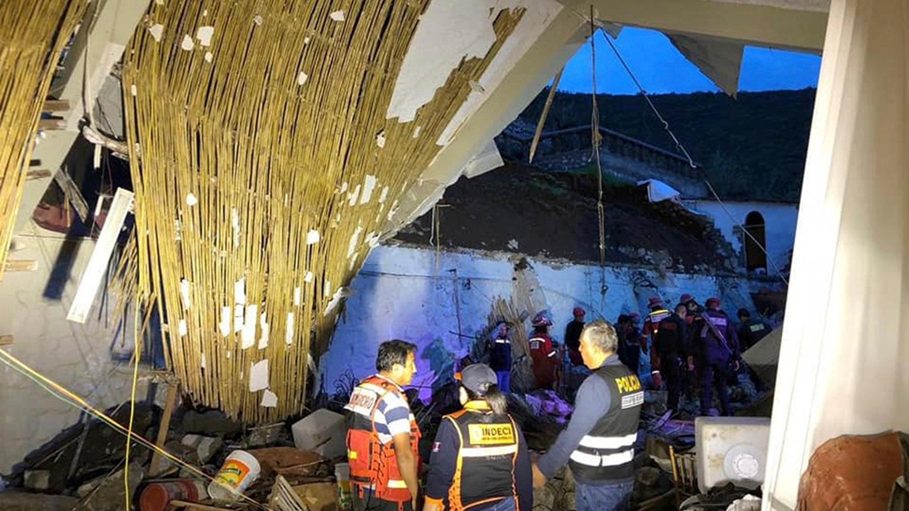 In this photo provide by Abancay police, officers and firefighters stand by a collapsed area of the Alhambra hotel in Abancay, Peru, Sunday, Jan. 27, 2019. (AP Photo/Abancay police via AP)