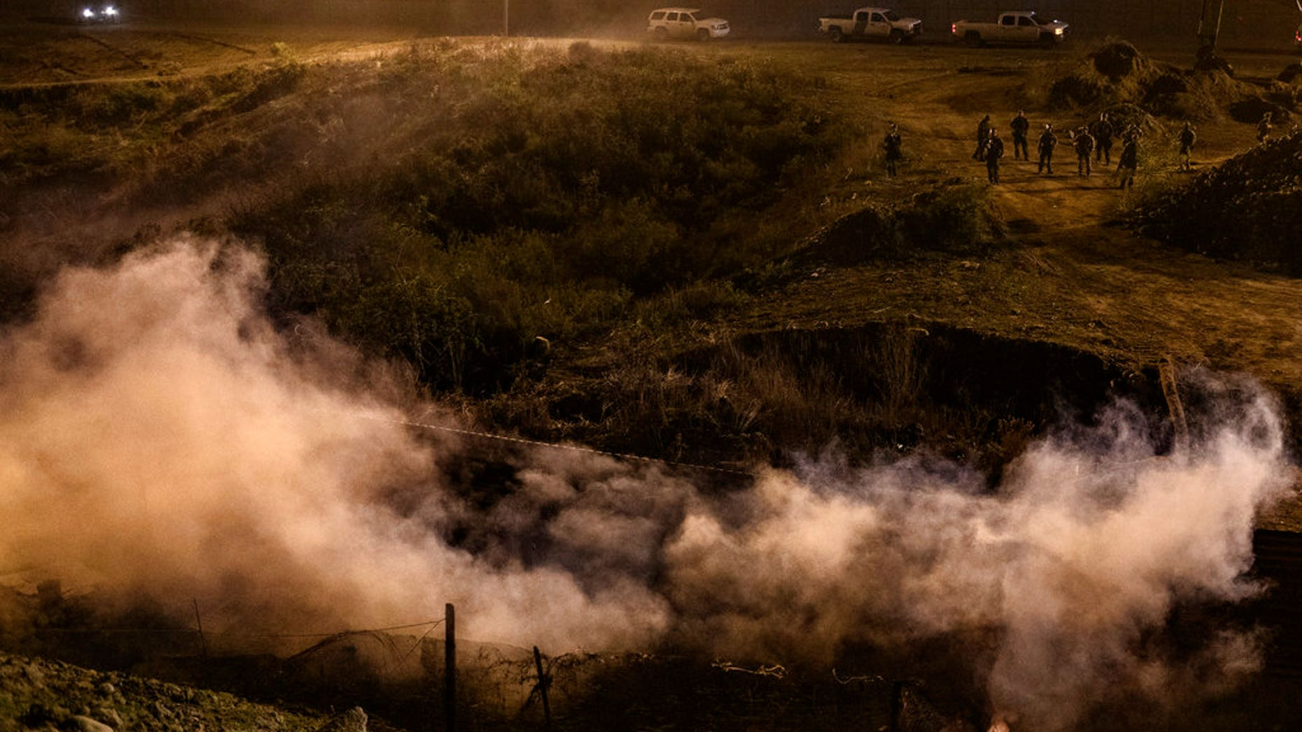 Migrants run as tear gas is thrown by U.S. Border Protection officers to the Mexican side of the border fence after they climbed the fence to get to San Diego on Tuesday. (Associated Press)