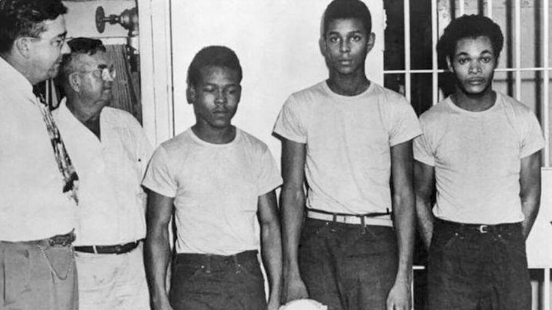 In this undated image released by the State Library and Archives of Florida, Lake County Sheriff Willis McCall, far left, and an unidentified man stand next to Walter Irvin, Samuel Shepherd and Charles Greenlee, from left, in Florida. The three men along with a fourth were charged with rape in 1949. Florida Gov. Ron DeSantis and a Cabinet granted posthumous pardons Friday, Jan. 11, 2019, to Shepherd, Irvin, Charles Greenlee and Ernest Thomas, the four African-American men accused of raping a white woman in 1949 in a case now seen as a racial injustice. (State Library and Archives of Florida via AP)