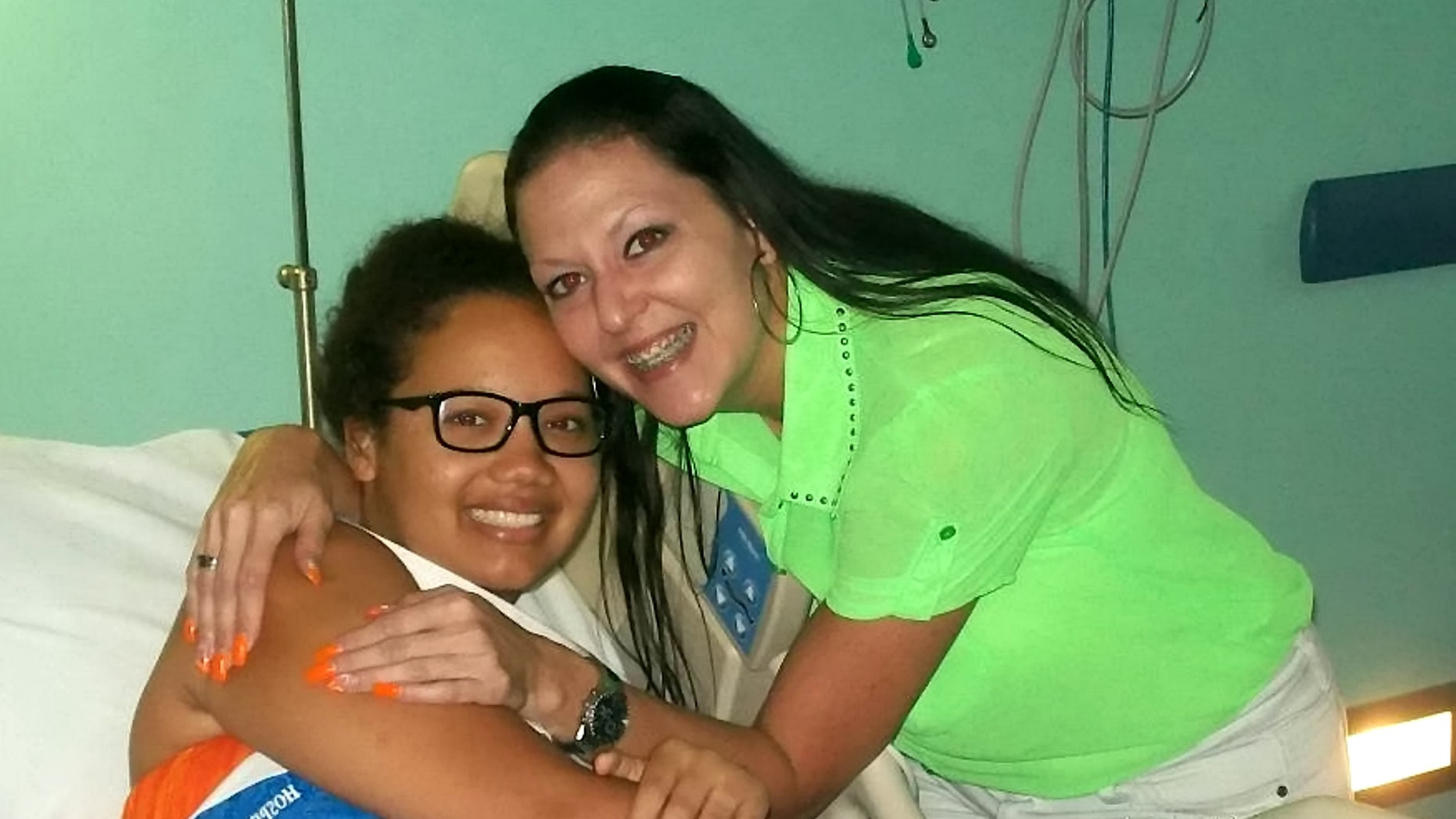 Gabrielle Newell, pictured with her aunt while in the hospital, said reconnecting with her faith in 2016 helped her find closure and forgiveness.