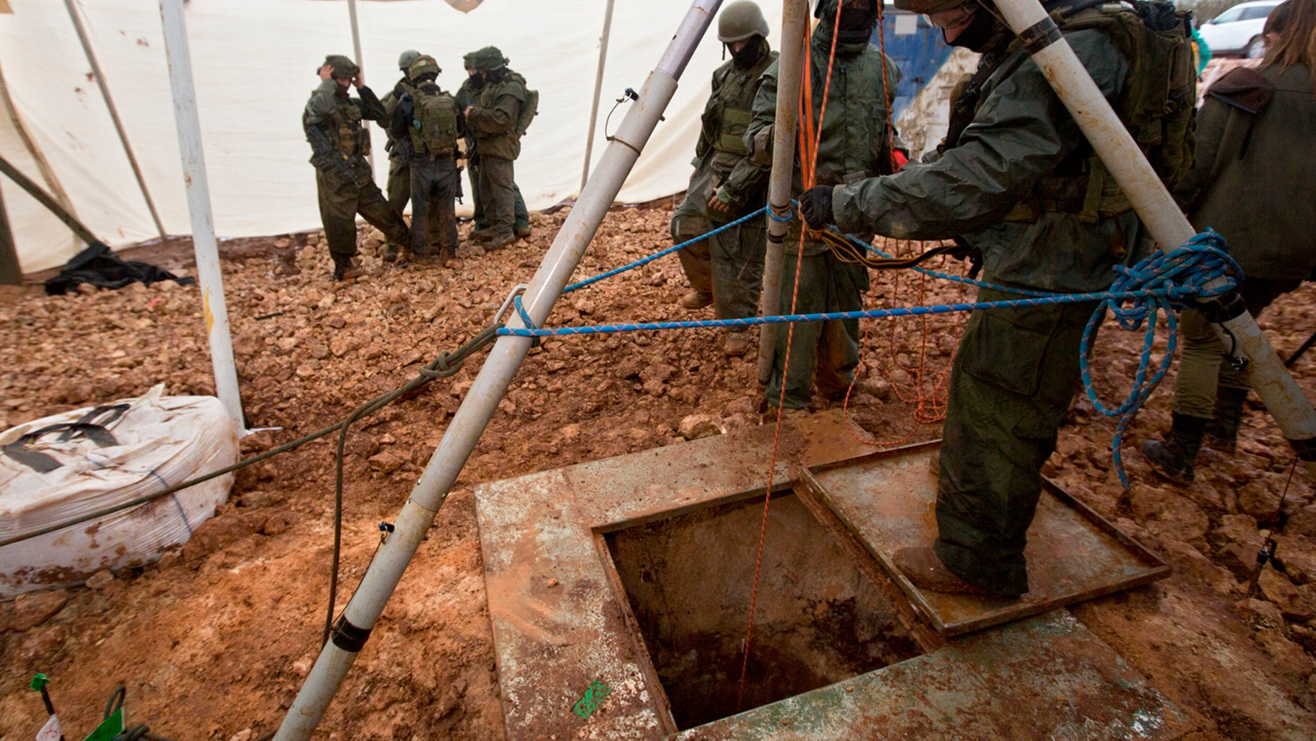 In this Wednesday, Dec. 19, 2018 file photo, Israeli soldiers stand around the opening of a hole that leads to a tunnel that the army says crosses from Lebanon to Israel, near Metula.