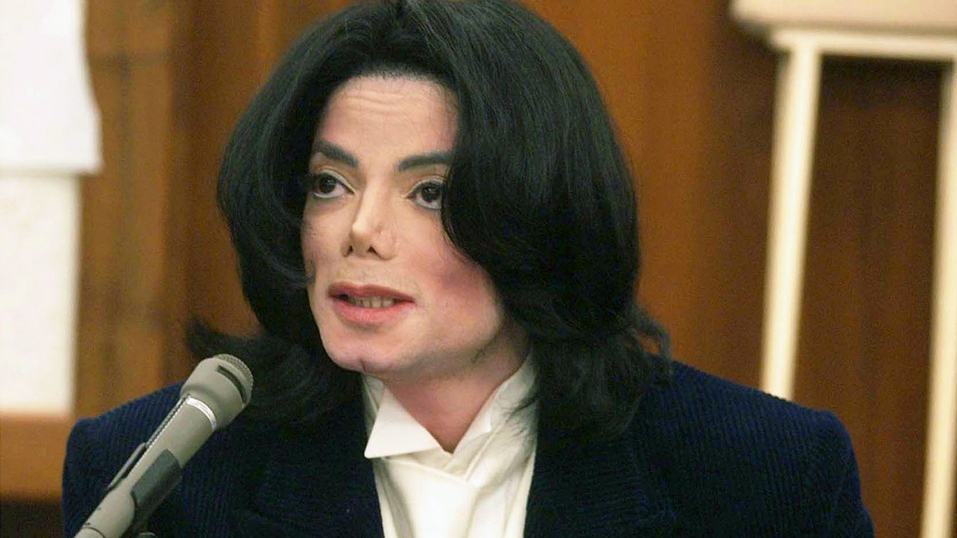 Michael Jackson speaks with photographers during a break in his testimony December 3, 2002 in Santa Maria, California. The late Jackson was being sued for $21 million for breach of contract over two millennium concerts. (Photo by Jim Ruymen - Pool/Getty Images)