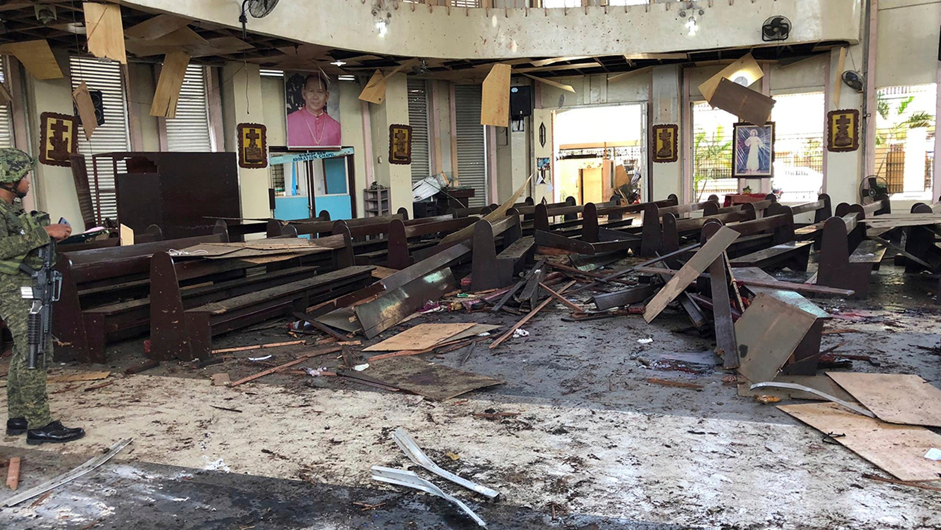 """A soldier looks at the site in a Roman Catholic cathedral in Jolo, the capital of Sulu province in the southern Philippines, after two bombs exploded on Sunday, January 27, 201<div class=""""e3lan e3lan-in-post1""""><script async src=""""//pagead2.googlesyndication.com/pagead/js/adsbygoogle.js""""></script> <!-- Text_Display_Responsive --> <ins class=""""adsbygoogle""""      style=""""display:block""""      data-ad-client=""""ca-pub-6192903739091894""""      data-ad-slot=""""3136787391""""      data-ad-format=""""auto""""      data-full-width-responsive=""""true""""></ins> <script> (adsbygoogle = window.adsbygoogle 