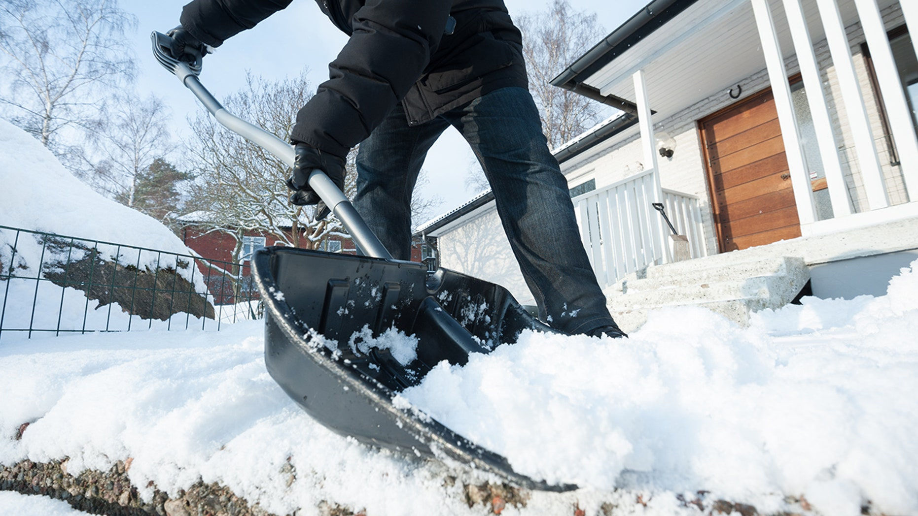 Man removing snow with a snow shovel in front of his house.