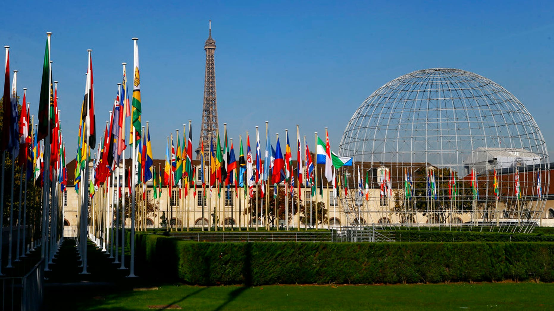 FILE - In this Tuesday Oct. 31, 2017 file picture, the Eiffel Tower, country flags and the Dome are seen from the garden of the United Nations Educational, Scientific and Cultural Organisation (UNESCO) headquarters building during the 39th session of the General Conference at the UNESCO headquarters in Paris, France. The United States and Israel have quit the U.N.'s educational, scientific and cultural agency, arguing the organization fosters anti-Israel bias. (AP Photo/Francois Mori, File)