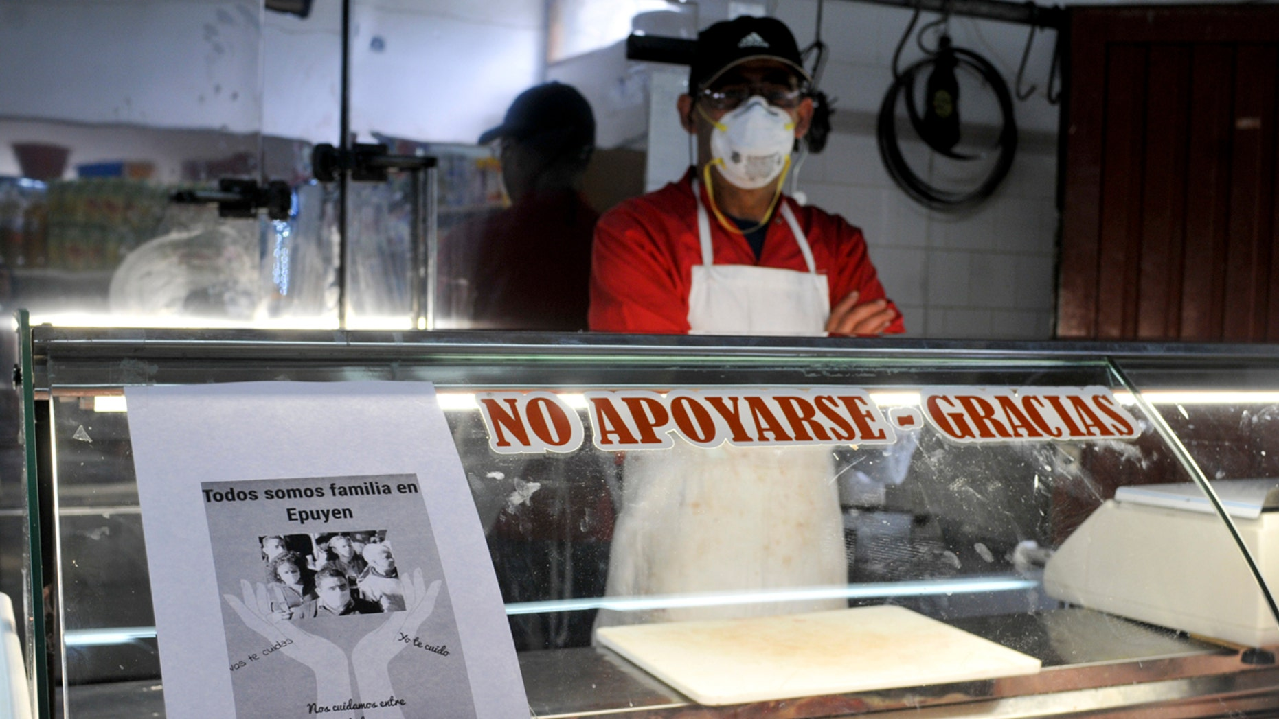 "A man wearing a mask waits for clients at his shop, with a sign posted that reads in Spanish ""We are all family in Epuyen, be supportive, use a mask"" in Epuyen, Argentina, Friday, Jan. 11, 2019. (AP Photo/Gustavo Zaninelli)"