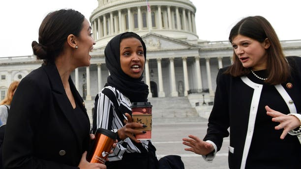 Rep. Alexandria Ocasio-Cortez, D-N.Y., left, talks with Rep. Ilhan Omar, D-Minn., center, and Rep. Haley Stevens, D-Mich., as they head to a group photo with the women of the 116th Congress on Capitol Hill last Friday. (AP Photo/Susan Walsh)